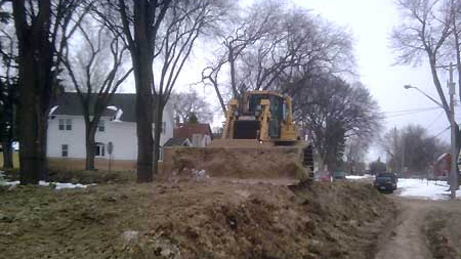 March 30: A Caterpillar bulldozer rests on top of a secondary levee in a downtown Fargo neighborhood near the Red River.