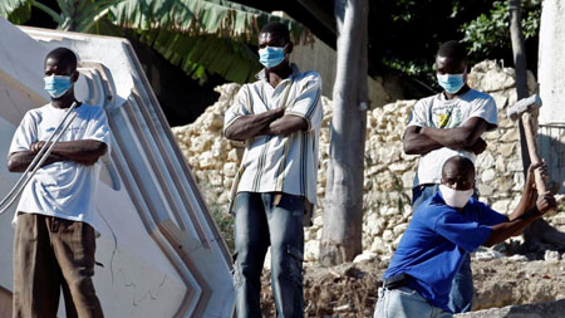 Jan. 14: Young men stand watch as another digs through debris in the shattered Haitian capital of Port-au-Prince. Tensions are rising as aid slowly filters in.