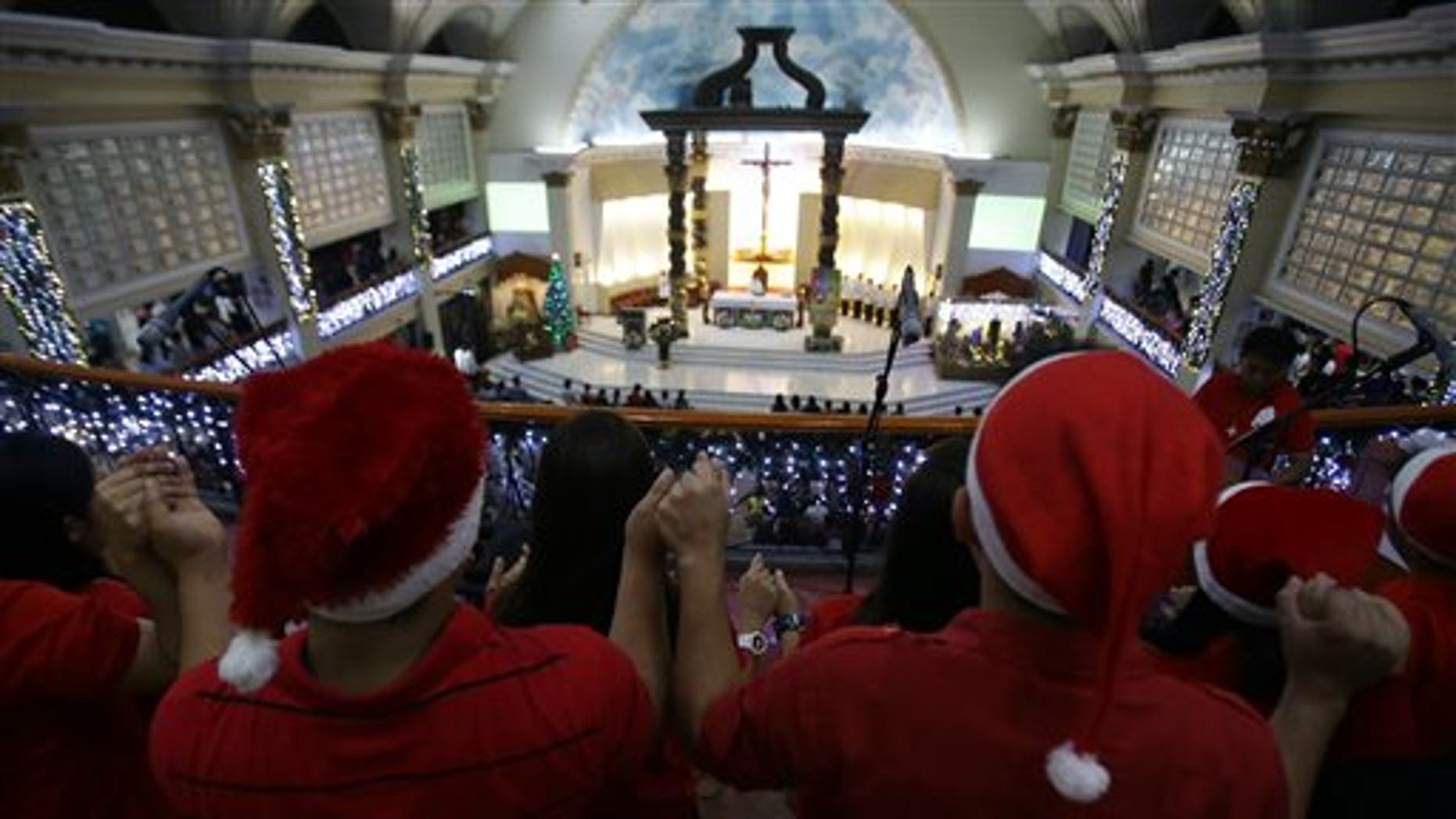 A Filipino Catholics choir hold hands as they sing during the first of nine daily dawn Masses before Christmas day at the St. Peter Parish in suburban Quezon city, north of Manila, Philippines on Wednesday, Dec. 16, 2015. This centuries-old tradition was said to have been started by farmers who wanted to fulfill their religious obligation before the day's work in the field. Christmas is the longest holiday celebration in this predominantly Roman Catholic nation.(AP Photo/Aaron Favila)