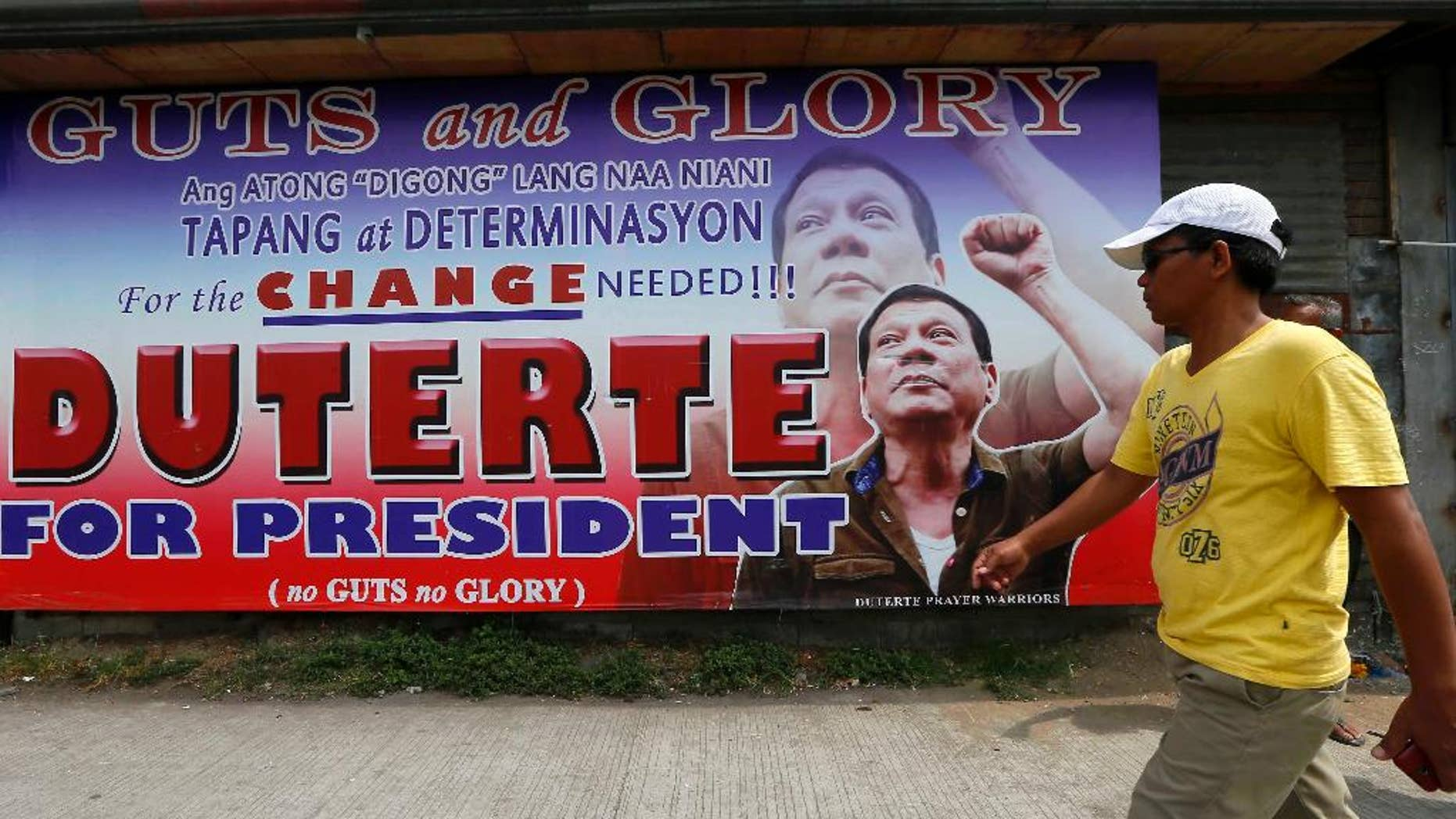 A resident walks past a campaign billboard of leading presidential candidate Mayor Rodrigo Duterte along a boulevard at his hometown in Davao city in southern Philippines Wednesday, May 11, 2016. Duterte has widened his lead in unofficial tally but still refuses to claim victory.(AP Photo/Bullit Marquez)