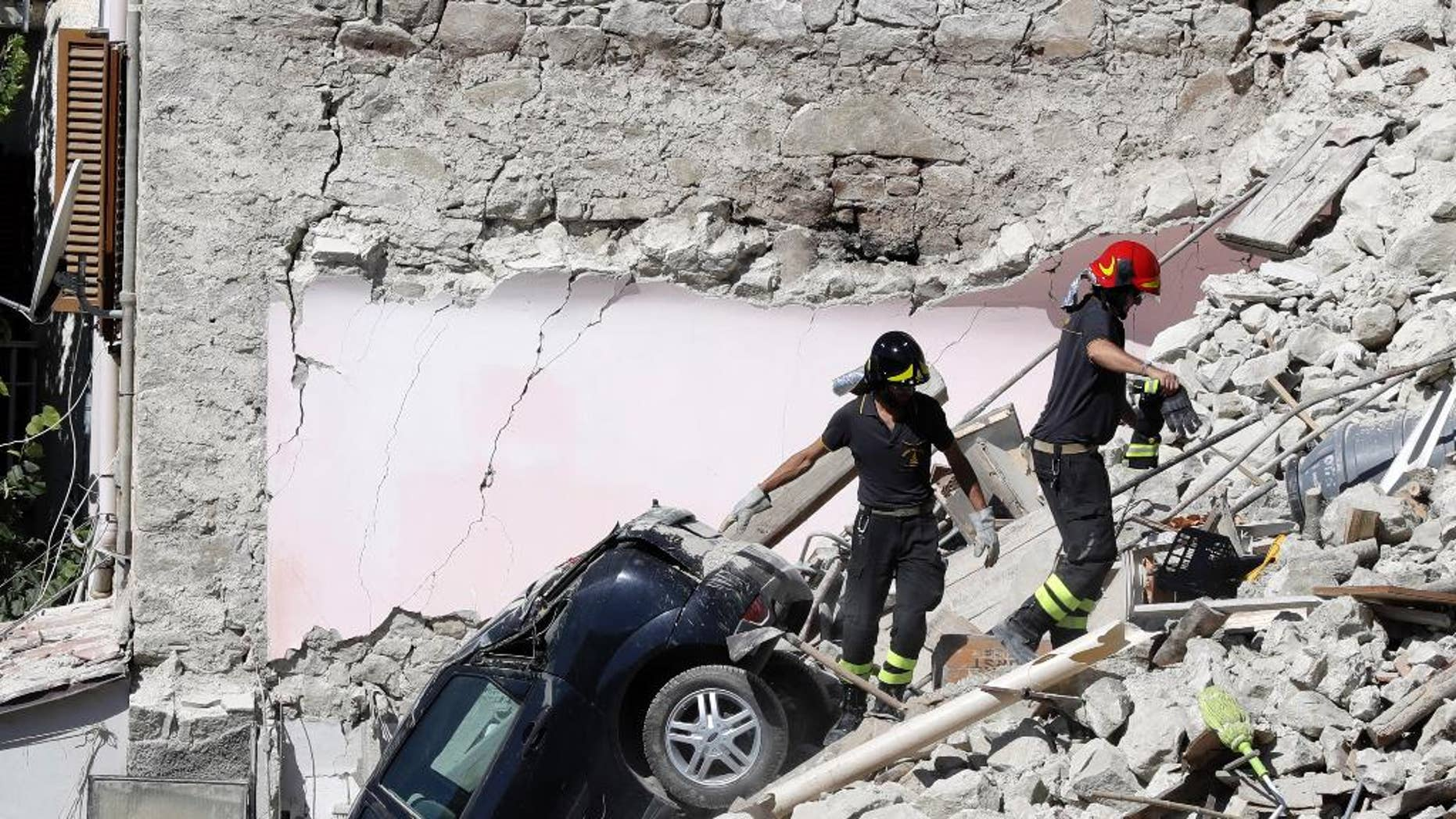 Rescuers make their way through destroyed houses following Wednesday's earthquake in Pescara Del Tronto, Italy, Thursday, Aug. 25, 2016. Rescue crews raced against time Thursday looking for survivors from the earthquake that leveled three towns in central Italy, but the death toll rose to 247 and Italy once again anguished over trying to secure its medieval communities built on seismic lands.  (AP Photo/Gregorio Borgia)