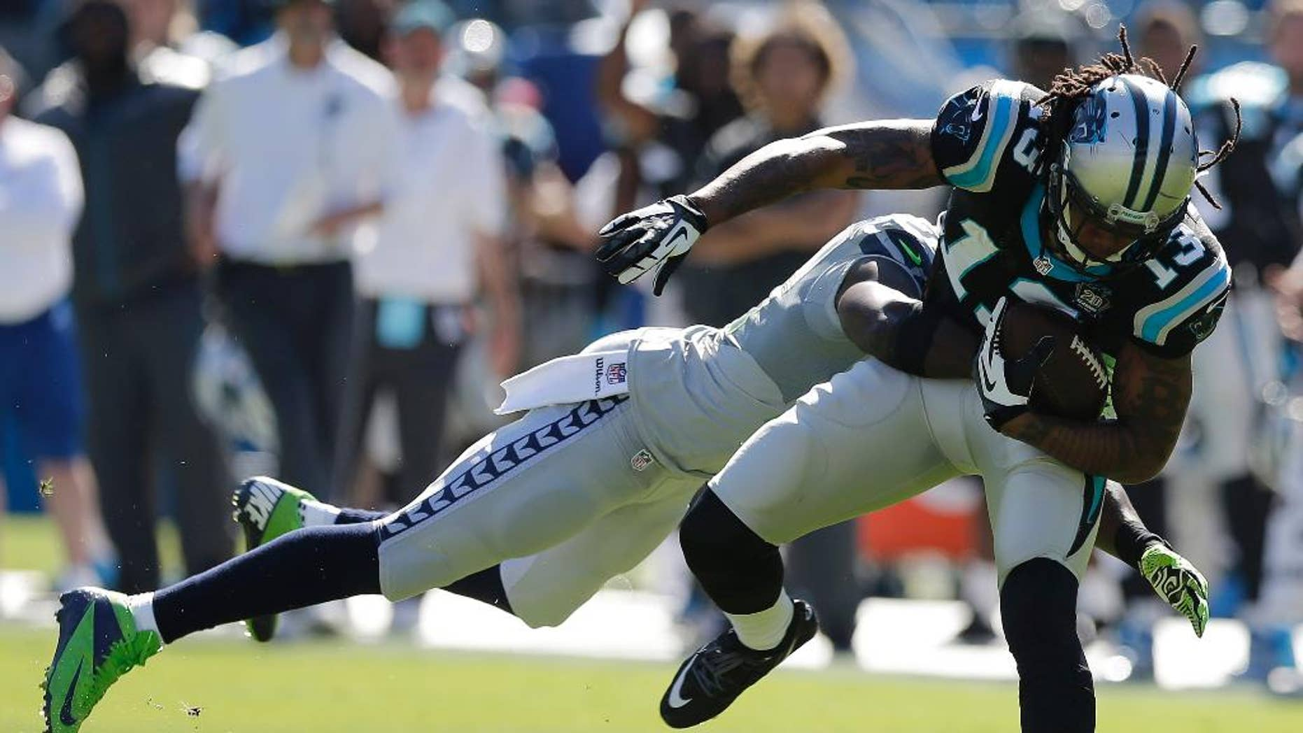 Carolina Panthers wide receiver Kelvin Benjamin (13) moves as Seattle Seahawks strong safety Kam Chancellor (31) tackles during the first half of an NFL football game, Sunday, Oct. 26, 2014, in Charlotte. (AP Photo/Chuck Burton)