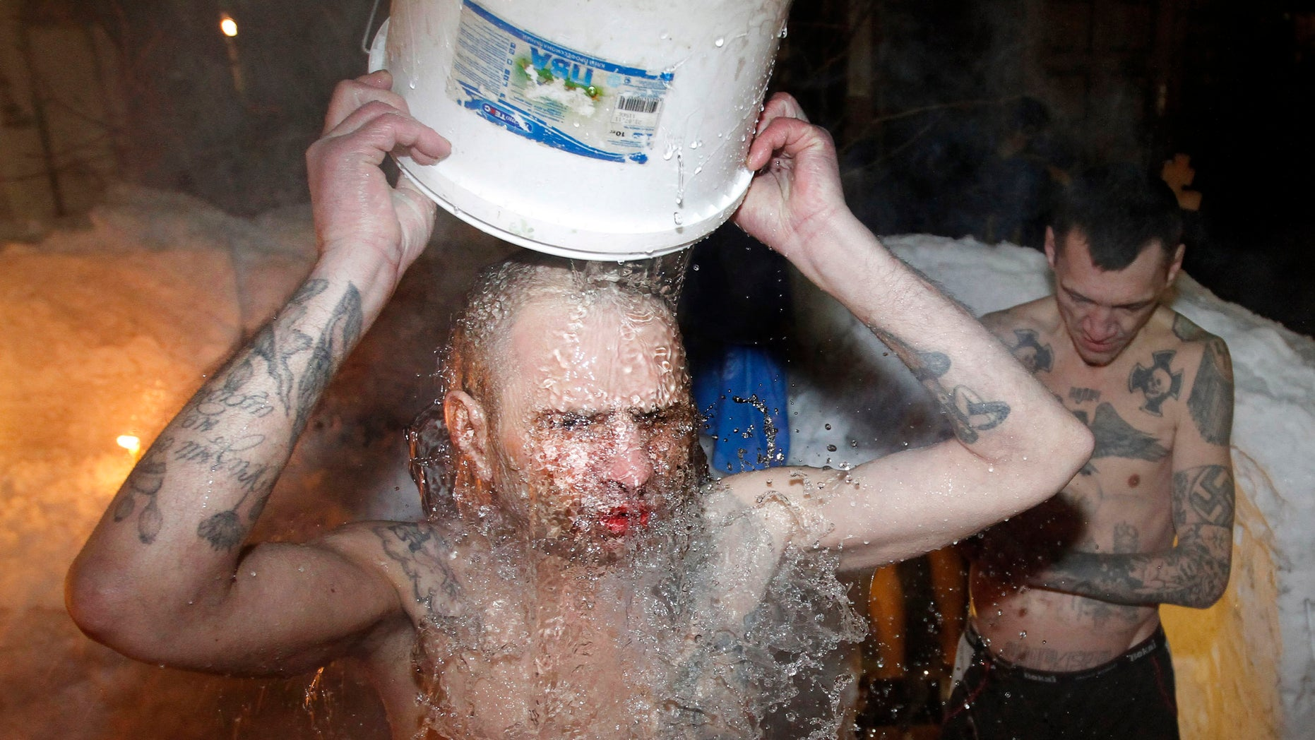 """FILE - In this file photo dated Thursday, Jan. 19, 2012, inmates of a prison colony pour cold water over themselves to celebrate Epiphany at St. Peter and Paul Cathedral in the Murmansk region of northern Russia.  The contract-style killing of Russian mobster Aslan Usoyan, also known as Grandpa Khasan, on Wednesday Jan16, 2013, drew renewed attention to the extensive and elaborate culture of the country's underworld figures who call themselves """"crowned thieves"""" and """"thieves in law.""""  Only top criminals are allowed to have tattoos which signal their privileged status within the criminal underworld, and may contain obscure codes, such as MIR (peace) meaning """"Only capital punishment will correct me, and the Nazi swastika means rejection of everything Soviet (but does not make its bearer a neo-Nazi). (AP Photo/ Andrey Pronin, FILE)"""