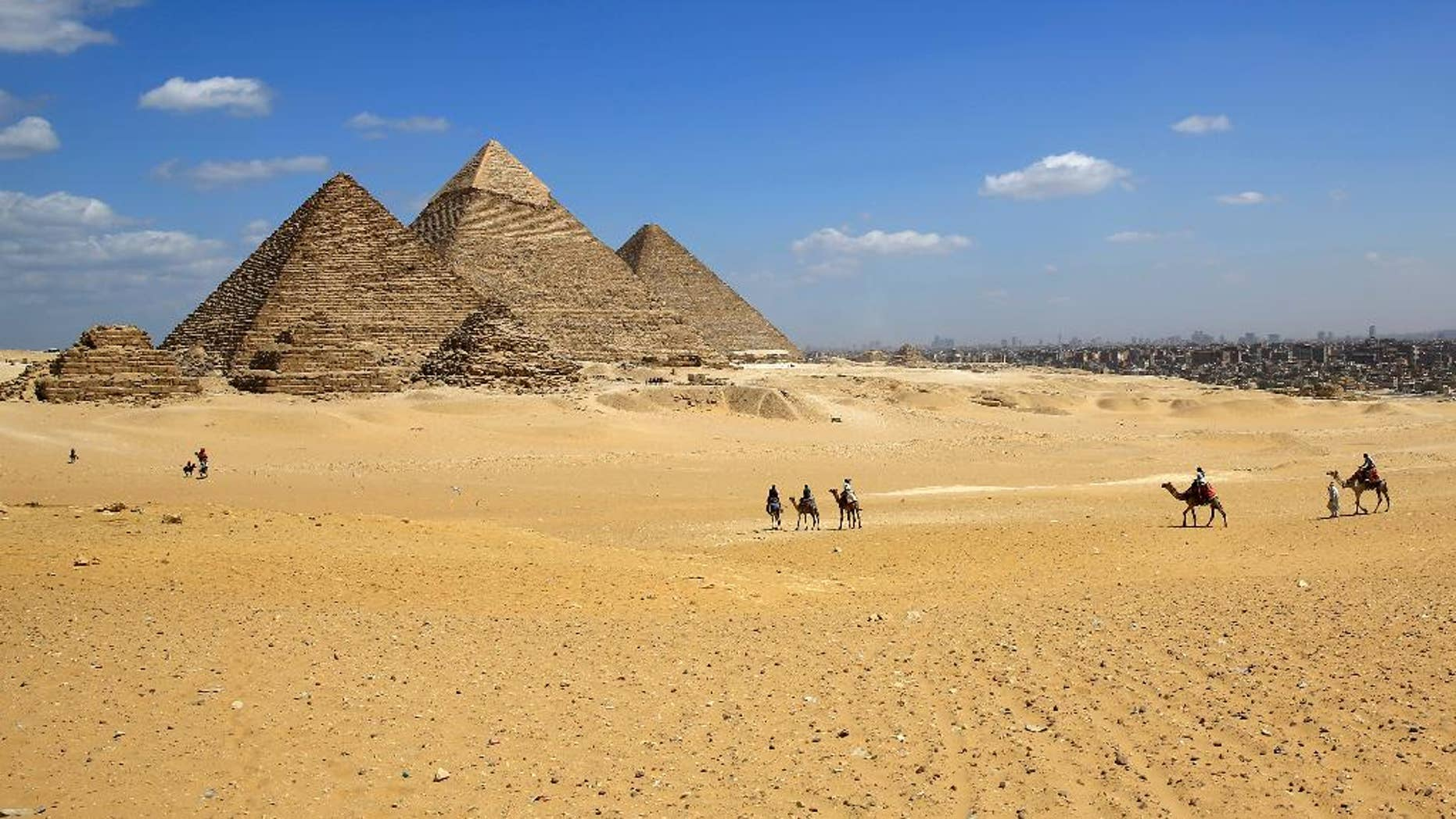 FILE - In this Thursday, April 9, 2015, file photo, tourists ride camels at the historical site of the Giza Pyramids in Giza, near Cairo, Egypt. Gunmen on a speeding motorcycle opened fire outside the plateau of the famed Giza Pyramids on the outskirts of Cairo early Wednesday, killing two policemen, in a rare attack near the country's tourist attractions, Egypt's state news agency and security officials said.  (AP Photo/Hassan Ammar)