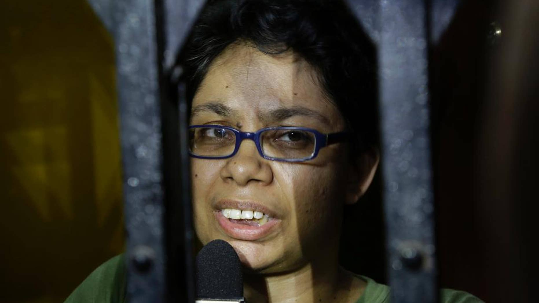 Agnes D'Souza, sister of Judith D'Souza who has allegedly been kidnapped in Afghanistan, talks to journalists from behind the front gate of their apartment in Kolkata, India, Friday, June 10, 2016. The 40-year-old worker was hired by the Aga Khan Foundation, which provides education and health assistance in about 30 countries. (AP Photo/ Bikas Das)