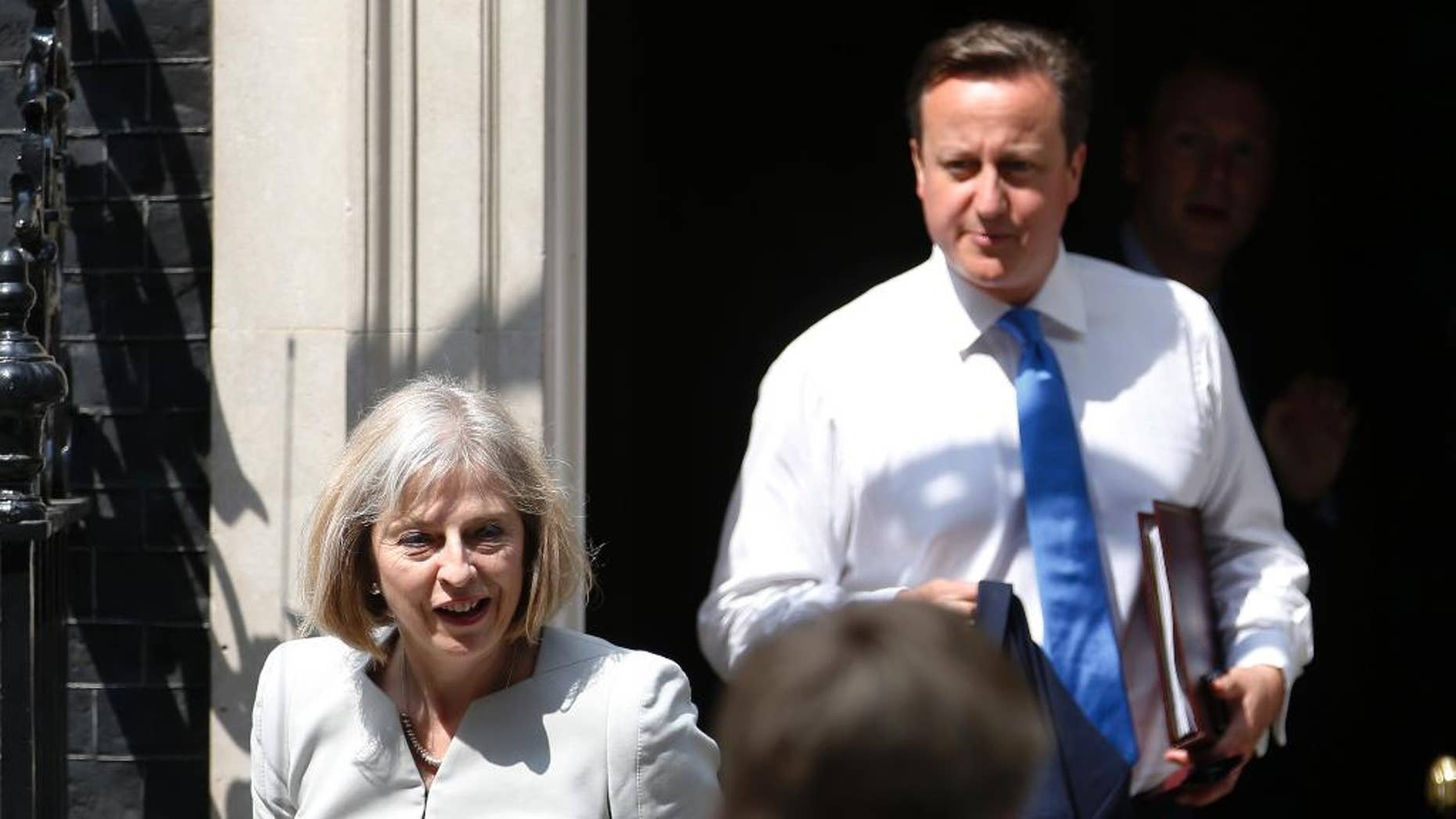 FILE - In this July 17, 2013 file photo, British Home Secretary Theresa May, left, and British Prime Minister David Cameron leave 10 Downing Street in London. A former senior British government official says May undermined Cameron in the run-up to Britain's June 23 referendum to leave the European Union. The accusation is levied in a serialization, published  Sunday, Sept. 25, 2016, of a book by Cameron's communications director, Craig Oliver. (AP Photo/Sang Tan, File)