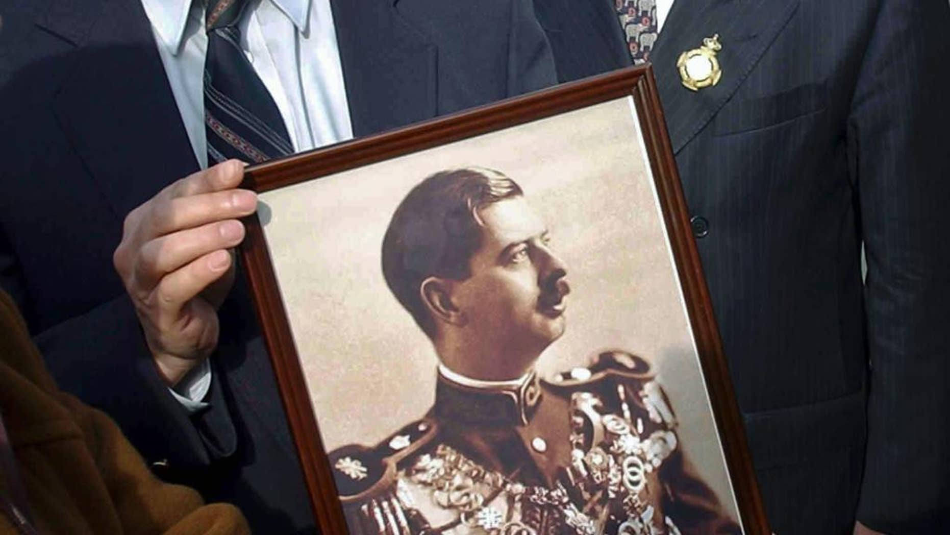 FILE - In this Feb.13 2003, file picture an unidentified man holds a photograph of Romania's King Carol II as Romania's Prince Paul, right, walks past outside a church in Lisbon, Portugal, where the king was buried.  Prosecutors have detained Romania's Prince Paul, Friday, Dec. 11, 2015, in a case of alleged real estate fraud involving a top aide to a former prime minister and a newspaper editor.(AP Photo/Armando Franca, File)