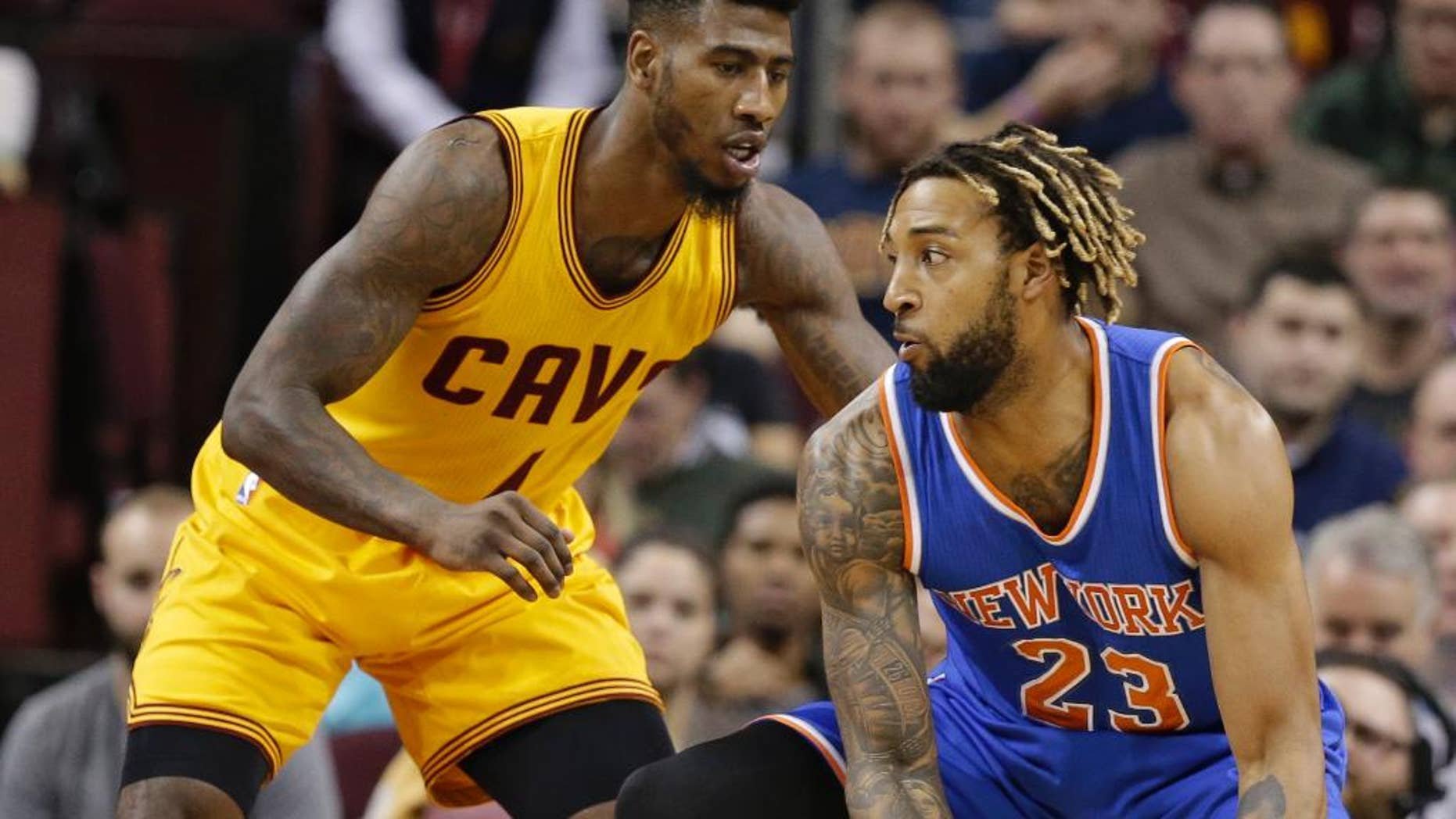New York Knicks' Derrick Williams (23) drives past Cleveland Cavaliers' Iman Shumpert (4) in the first half of an NBA basketball game Wednesday, Dec. 23, 2015, in Cleveland. The Cavaliers won 91-84. (AP Photo/Tony Dejak)