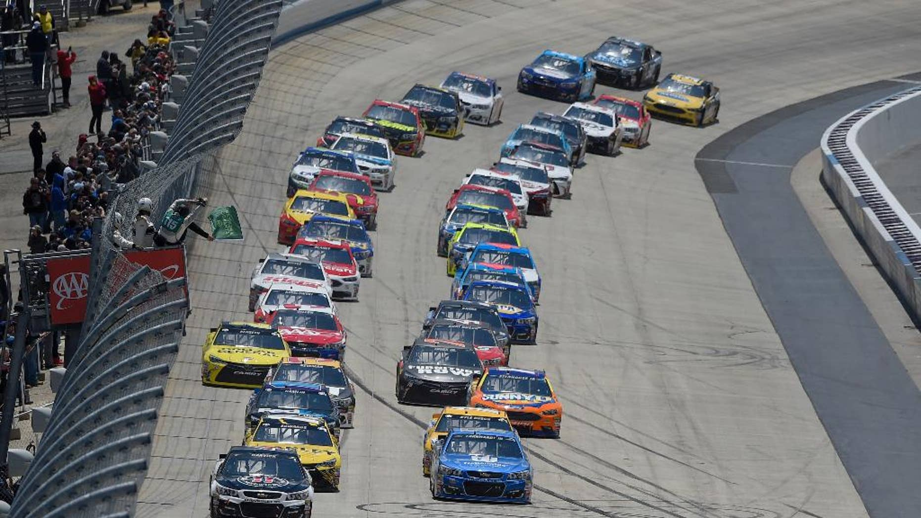 Kevin Harvick, front left, and Dale Earnhardt Jr., front right, lead the field to take the green flag to start the NASCAR Sprint Cup series auto race, Sunday, May 15, 2016, at Dover International Speedway in Dover, Del. (AP Photo/Nick Wass)