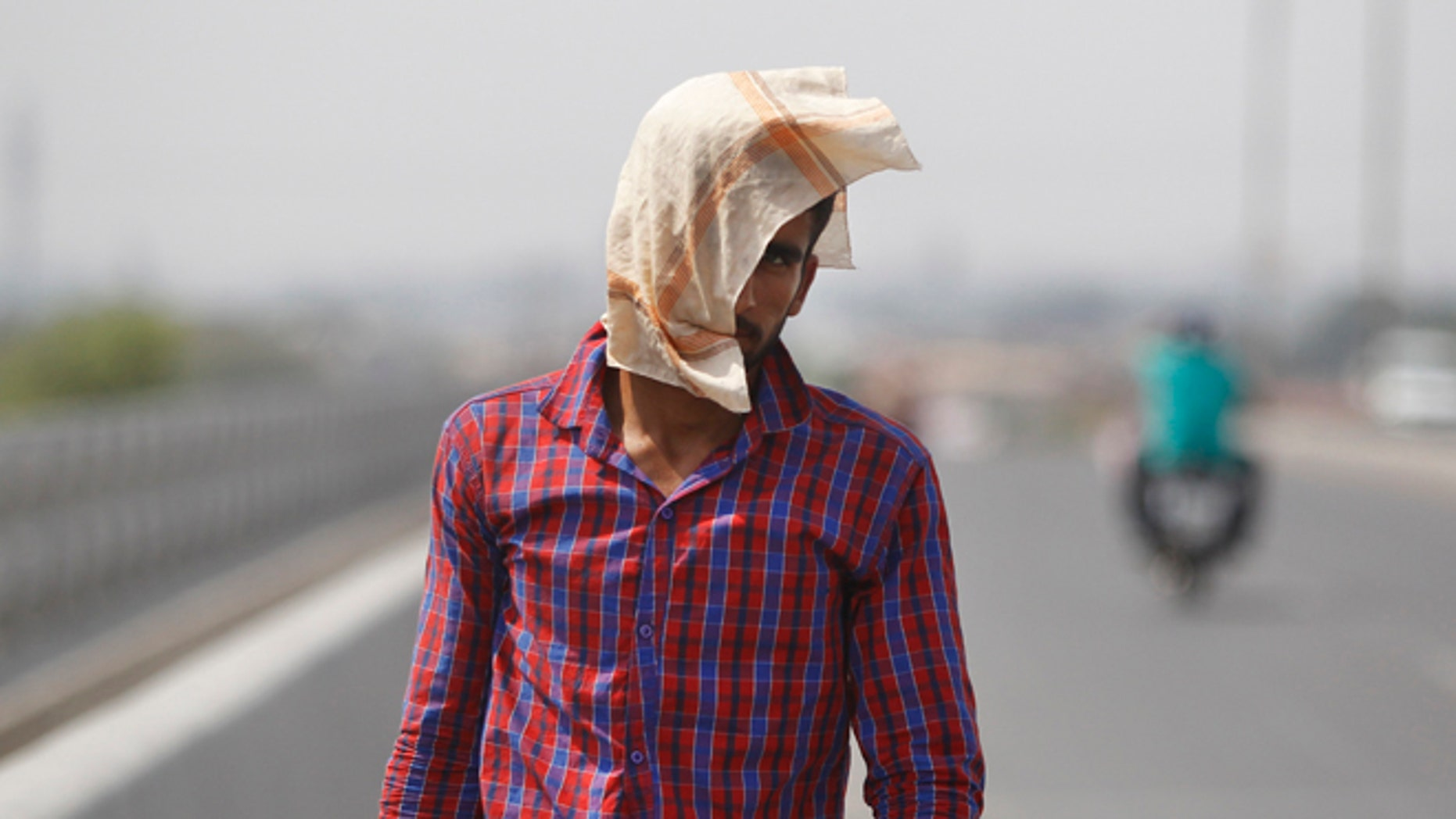 A man uses a cloth to protect himself from the sun during a hot summer day in Jammu, India, Friday, May 20, 2016. The prolonged heat wave this year has already killed hundreds and destroyed crops in more than 13 states, impacting hundreds of millions of Indians. (AP Photo/Channi Anand)