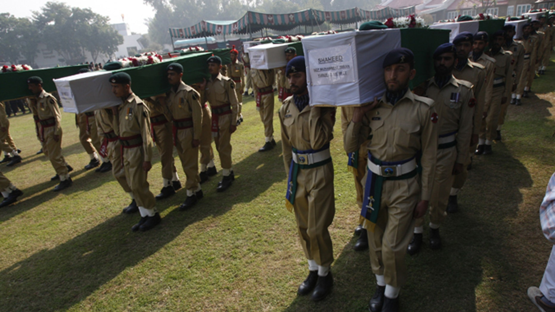 Nov. 27: Pakistan army soldiers carry coffin of Saturday's NATO attack victims for funeral in Peshawar, Pakistan.