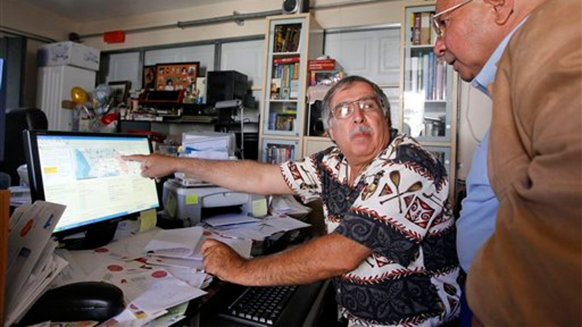 In this June 15, 2011 photo, Art Montez, left, and Reben Treviso look at potential congressional redistricting maps on Montez's home computer, in Buena Park, Calif.  The debate over redistricting proposals by the independent commission will escalate in the coming weeks, as the panel takes public comment and wrestles with revisions before voting on a final version Aug. 15.   (AP Photo/Chris Carlson)