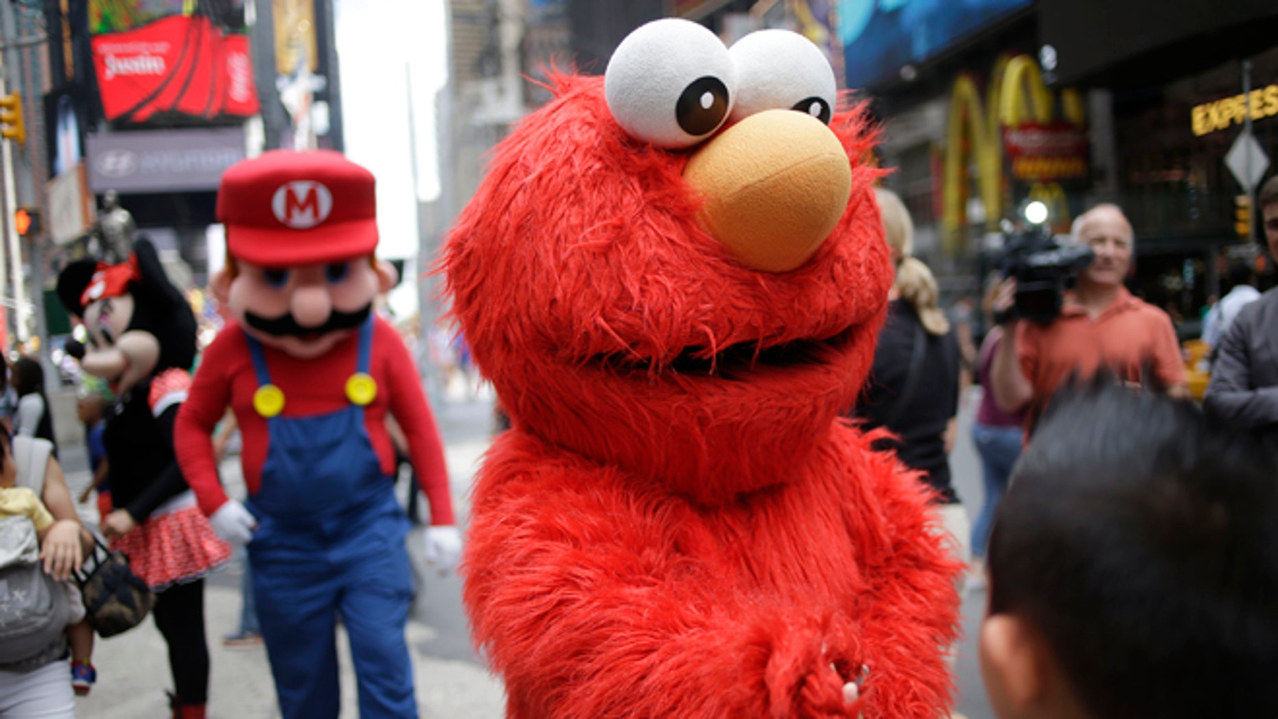 A person dressed as Elmo shakes hands with a pedestrian in Times Square on Monday, July 28, 2014 in New York. New York City Mayor Bill de Blasio said Monday that he believes the people wearing character costumes in Times Square should be licensed and regulated. Dozens of people dressed as kids favorites like Elmo, Cookie Monster and Batman stand near 42nd Street and pose for photos with tourists in exchange for money. De Blasio said the practice has gone too far.  A man dressed as Spider-man was arrested Saturday, July 28, 2014, after punching a police officer who told him to stop harassing tourists.  The City Council is working on legislation that would require the characters to get a city-approved license.  (AP Photo/Seth Wenig)