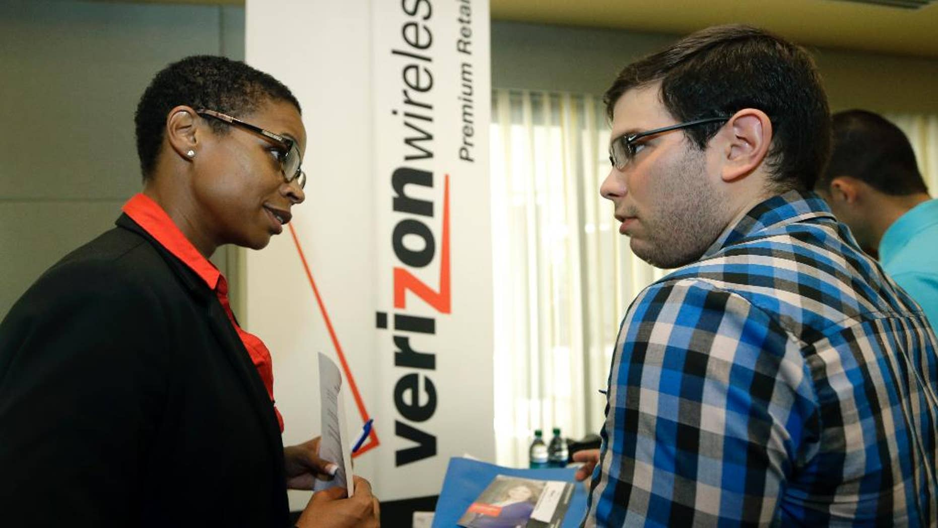 In this July 15, 2015, photo, Sasha Vitalis, left, talks about job opportunities to job seeker Omar Delgado at a job fair in Miami Lakes, Fla. Payroll processor ADP reports how many jobs private employers added in July on Wednesday, Aug. 4, 2015. (AP Photo/Alan Diaz)