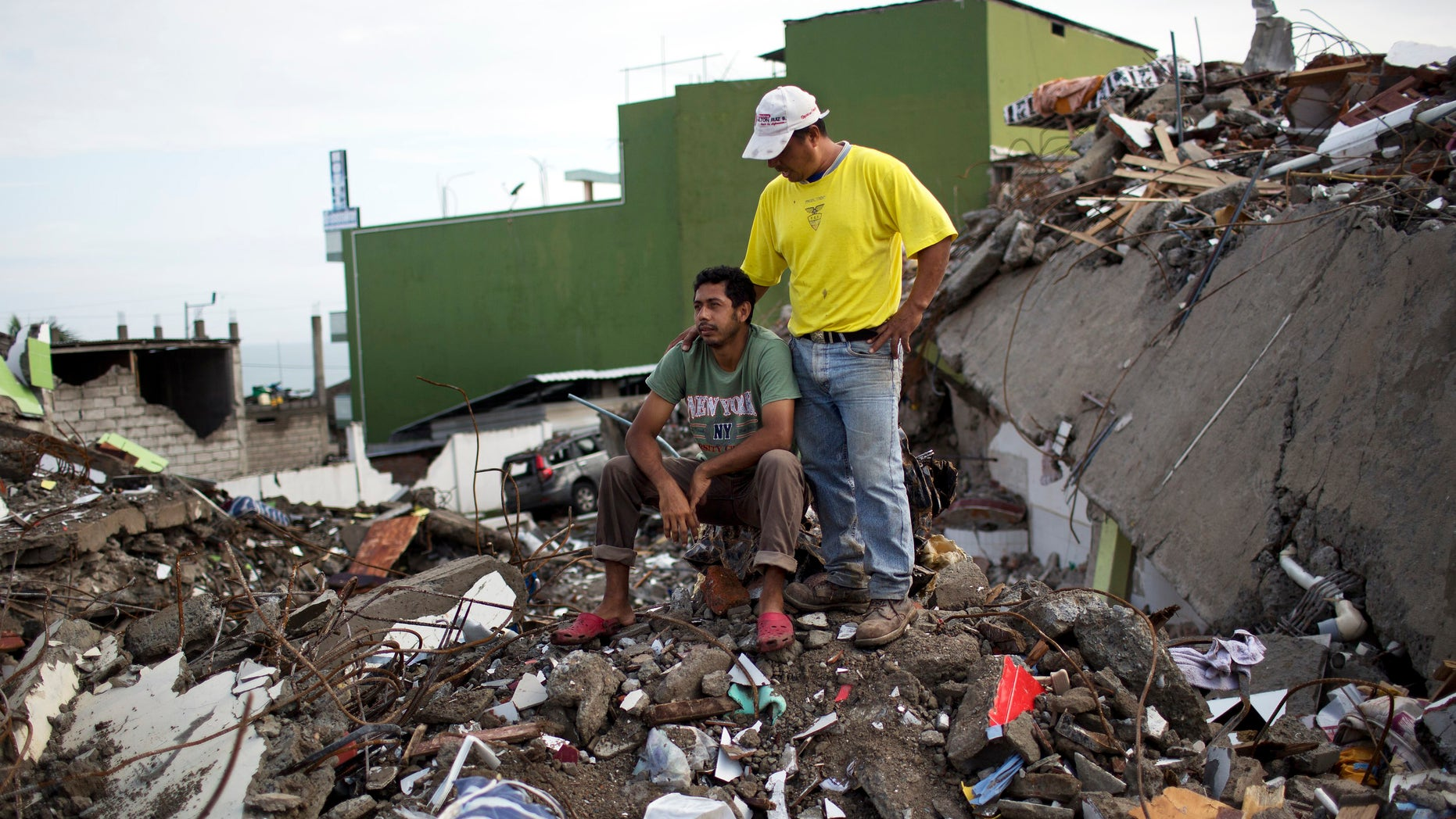 Roberto Ganchoso is comforted by a neighbor as he sits on what's left of his neighborhood, as he watches a bulldozer demolish the hotel next door to his property in Pedernales, Ecuador, Saturday, April 23, 2016. President Rafael Correa has said the earthquake caused $3 billion in damage and warned that the reconstruction effort will take years. His administration is temporarily raising taxes to fund the recovery. (AP Photo/Rodrigo Abd)