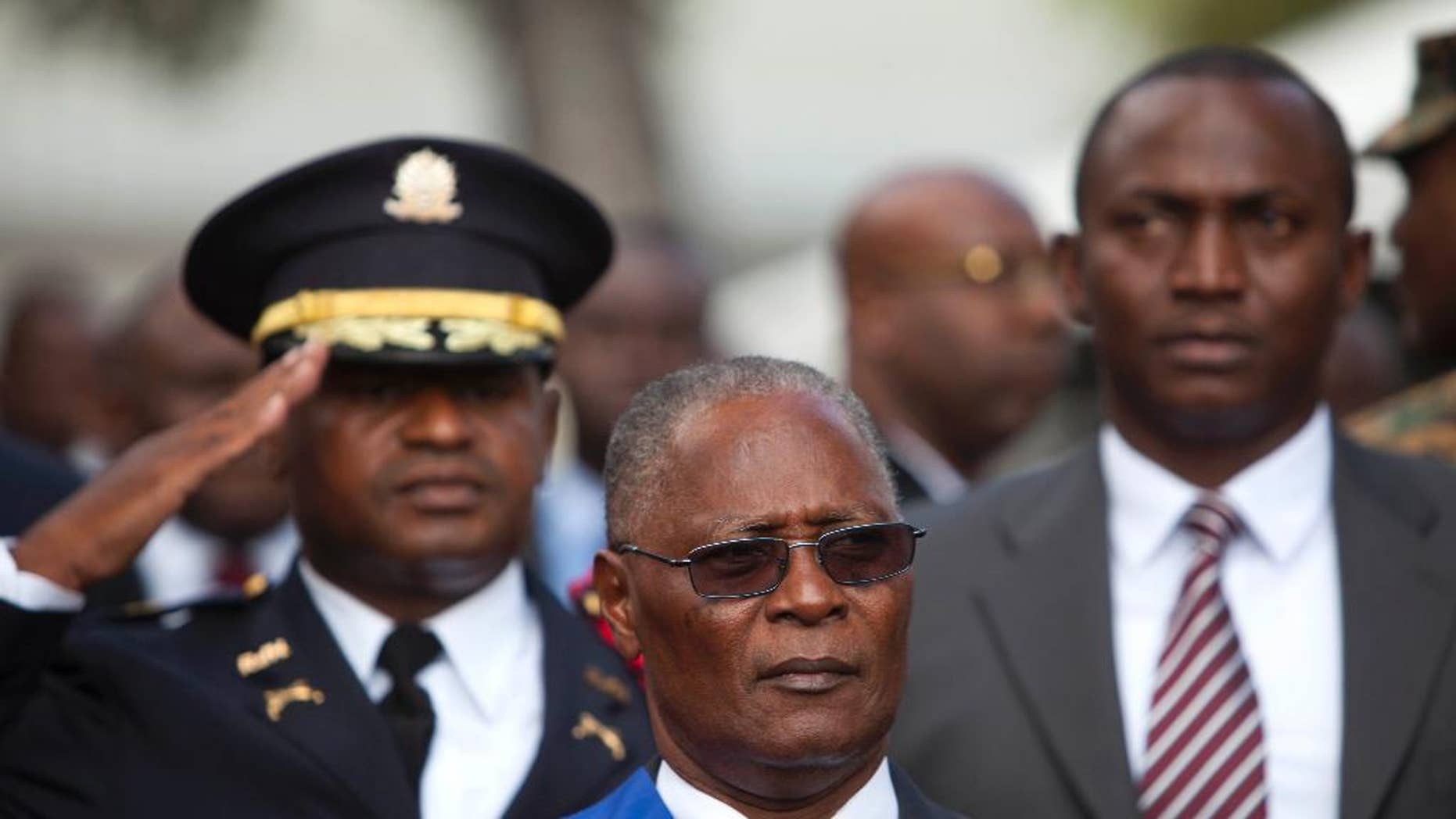 FILE - In this Feb. 14, 2016, file photo, Haiti's provisional President Jocelerme Privert stands for the national anthem after delivering his speech at an installation ceremony, in Port-au-Prince, Haiti. Haiti's deeply divided lawmakers met at the National Assembly but were unable to make progress toward a vote on the interim president's mandate which expired two weeks ago. The fruitless session began Tuesday, June 28 and was adjourned early Wednesday. (AP Photo/Dieu Nalio Chery, File)