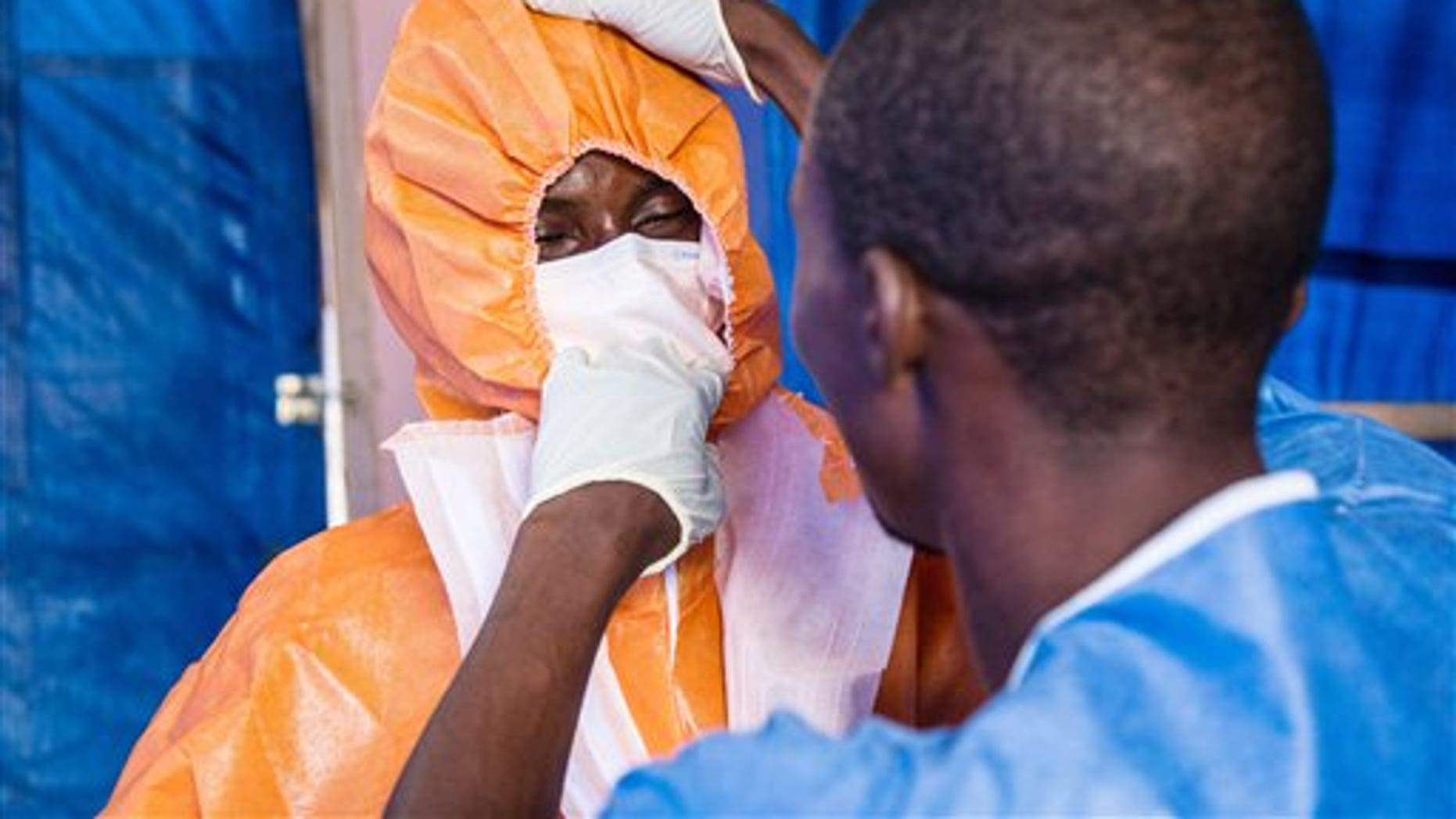 Healthcare workers wear protective gear before entering into an Ebola treatment centre in Hastings, Freetown, Sierra Leone, Wednesday, Oct. 15, 2014. Some doctors in countries hit hardest by the deadly Ebola disease decline to operate on pregnant women for fear the virus could spread. Governments face calls from frightened citizens to bar travel to and from the afflicted region. Meanwhile, the stakes get higher as more people get sick, highlighting a tricky balance between protecting people and preserving their rights in a global crisis. (AP Photo/Michael Duff)