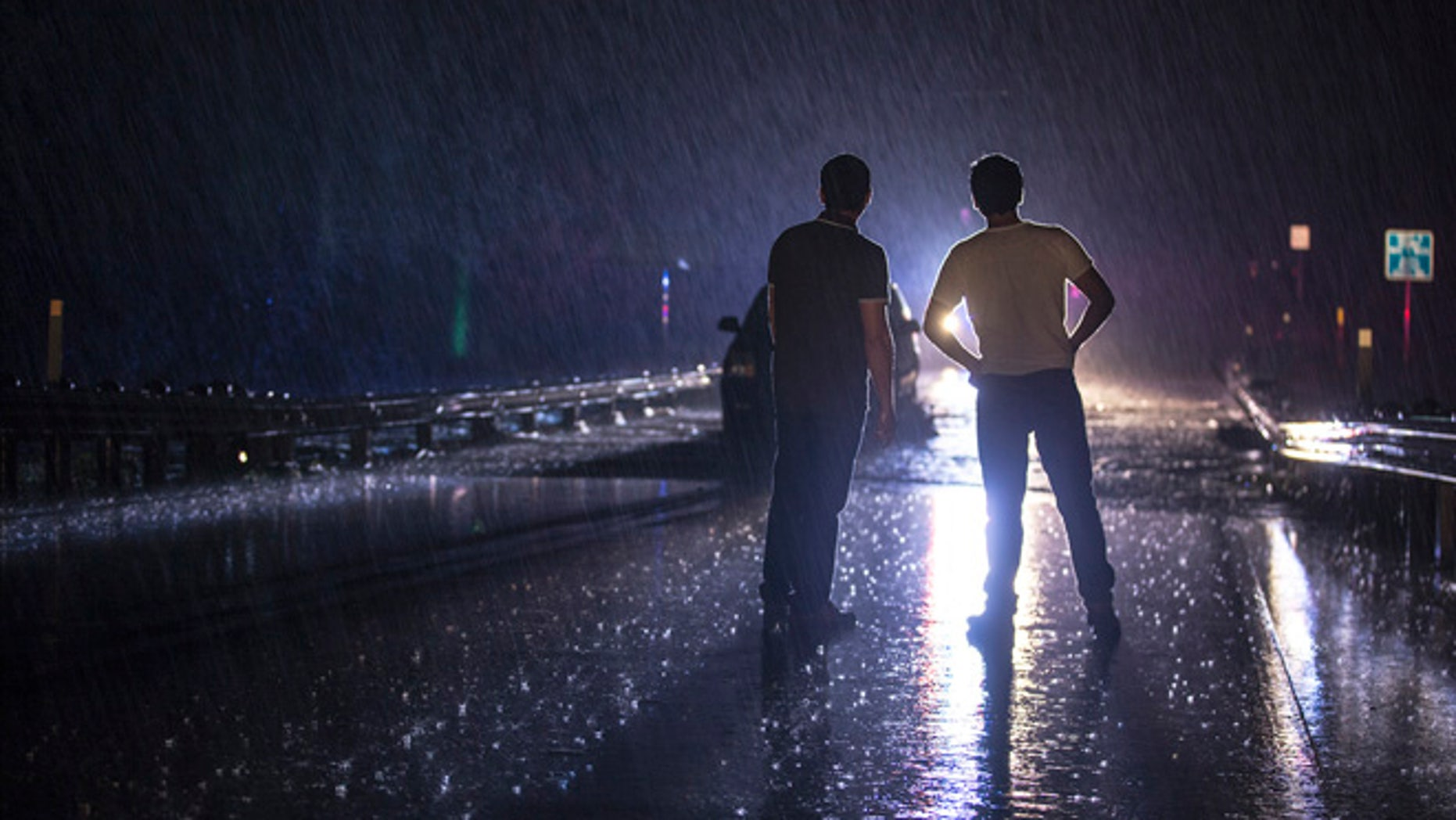 Two men stand on the Dry Creek bridge as they look on at a stranded vehicle from the rising flood water in Austin, Texas, early Friday morning, May 27, 2016. (Ricardo B. Brazziell/Austin American-Statesman via AP)