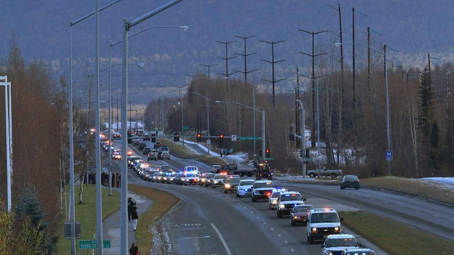 A motorcade of police, fire and emergency responder vehicles escorts a car carrying the body of Fairbanks Police Sgt. Allen Brandt to Ted Stevens Anchorage International Airport for a flight to Fairbanks on Tuesday, Nov. 1, 2016, in Anchorage, Alaska. Brandt was on duty Oct. 16 when he was shot six times. He died Friday in Anchorage after complications from surgery. His funeral is scheduled for Sunday in Fairbanks. (AP Photo/Dan Joling)