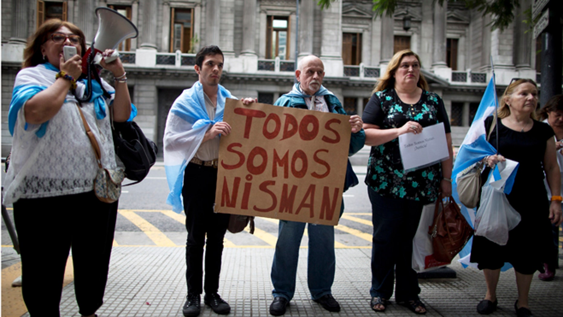 """People holding a sign that reads in Spanish """"We are all Nisman,"""" protest the death of special prosecutor Alberto Nisman, outside Congress in Buenos Aires, Argentina, Monday, Jan. 19, 2015. Nisman who accused the government of secret deals with Iran over an investigation into a 1994 Argentine-Israeli Mutual Association community center terrorist attack, was found dead with a gunshot wound, at his apartment early Monday. Nisman was due to participate in a closed-door session with Congress Monday over his claim last week that Argentine President Cristina Fernandez and Foreign Minister Hector Timerman covered up a deal with Iran. (AP Photo/Rodrigo Abd)"""