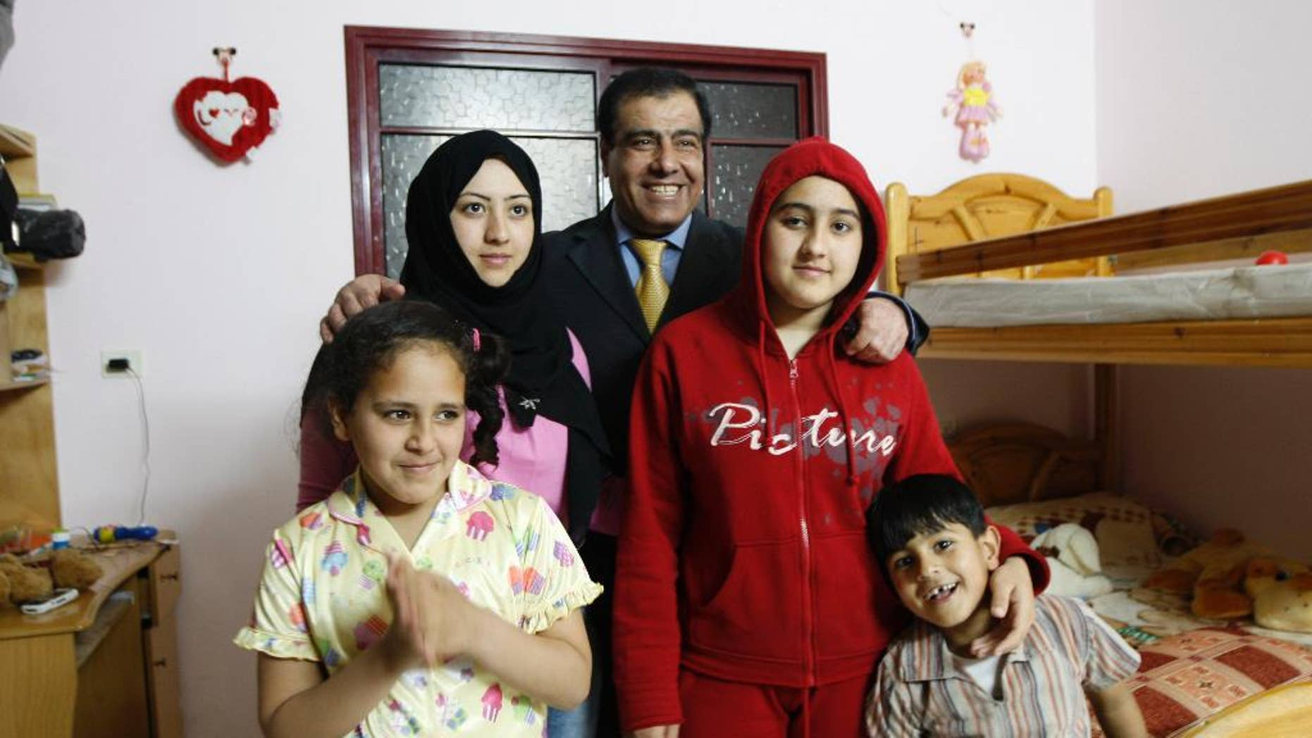 """FILE - In this May 7, 2009 file photo, Palestinian Dr. Izzeldin Abuelaish poses for a picture with his children in his house in Jebaliya, northern Gaza Strip. Dr. Abuelaish has made an emotional appeal to Israel to apologize for killing three of his daughters and a niece in a 2009 shelling attack on his Gaza home, speaking on the eve of a hearing in his civil suit, urged the state Tuesday to """"take responsibility."""" (AP Photo/Khalil Hamra, File)"""