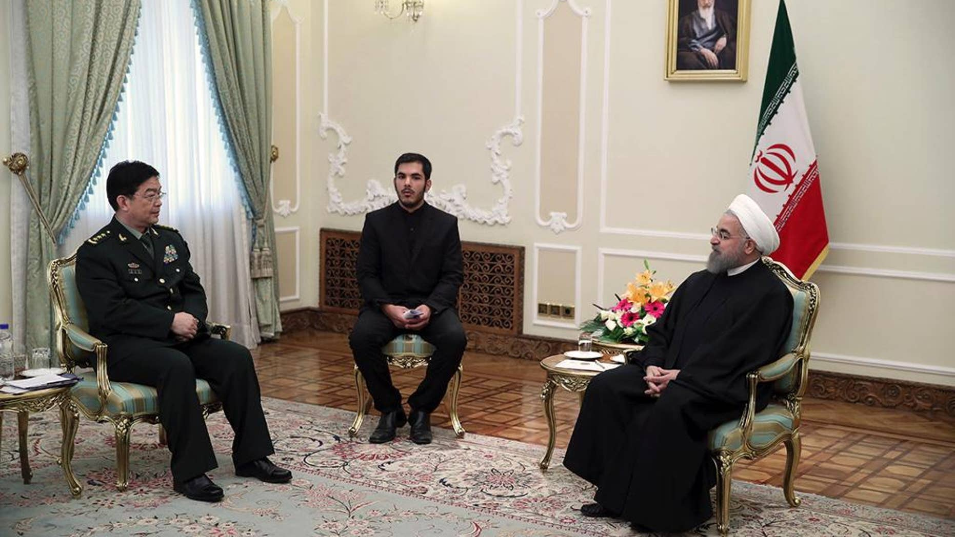 In this photo released by an official website of the office of the Iranian Presidency, President Hassan Rouhani, right, meets with Chinese Defense Minister Chang Wanquan, left, at his office, in Tehran, Iran, Tueday, Nov. 15, 2016. An unidentified interpreter sits at center. (Iranian Presidency Office via AP)