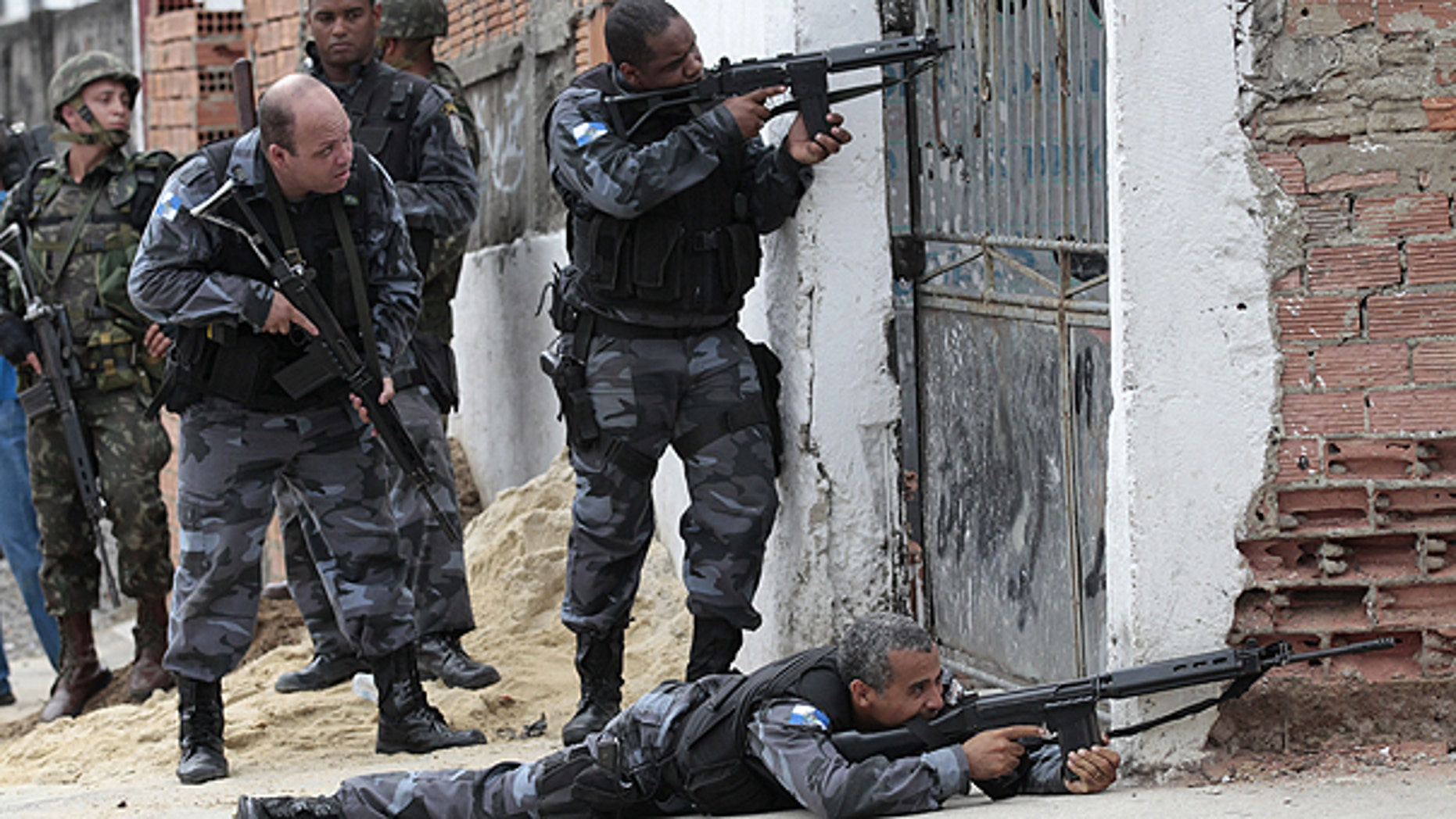 Nov. 26: Policemen take position during an operation against drug traffickers at the Complexo de Alemao slum in Rio de Janeiro, Brazil.