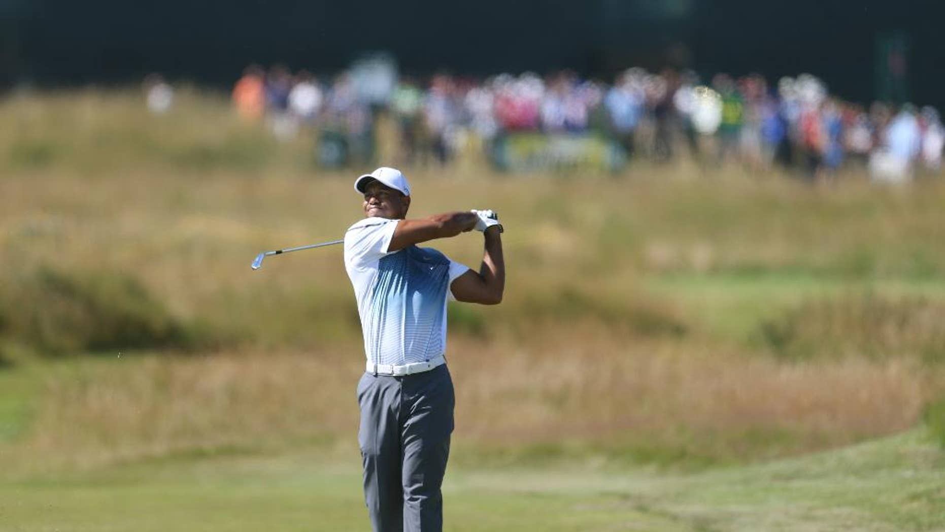Tiger Woods of the US plays a shot on the 2nd fairway during the first day of the British Open Golf championship at the Royal Liverpool golf club, Hoylake, England, Thursday July 17, 2014. (AP Photo/Peter Morrison)