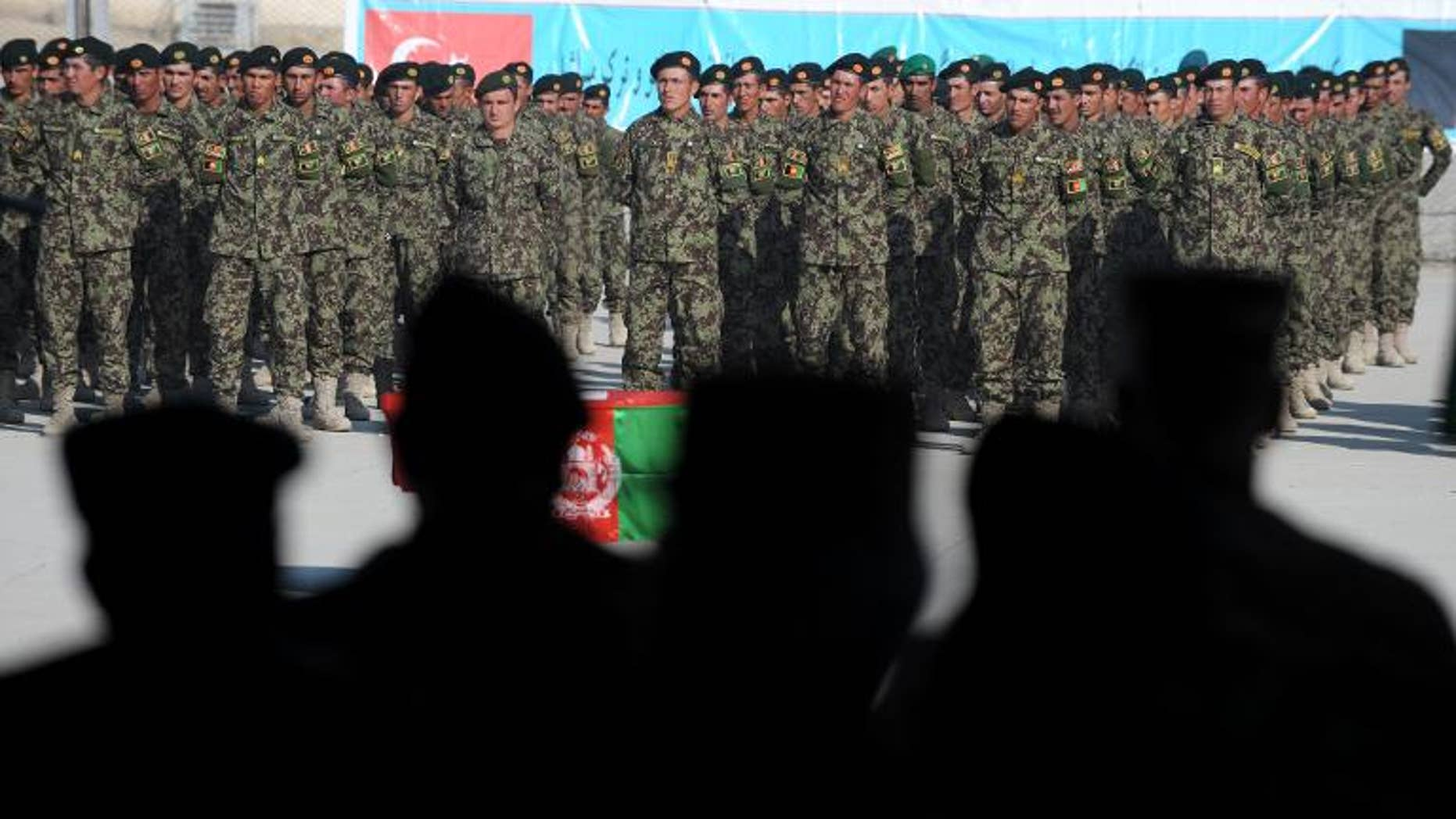 Afghan and International Security Assistance Force (ISAF) officers watch Afghan National Army (ANA) cadets during a graduation ceremony in Kabul on December 15, 2011.