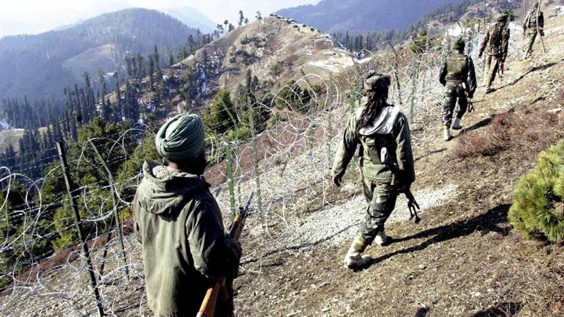 Indian soldiers on patrol along a barbed-wire fence in Baras, on December 4, 2003 -- near the Line of Control (LoC) that divides Kashmir
