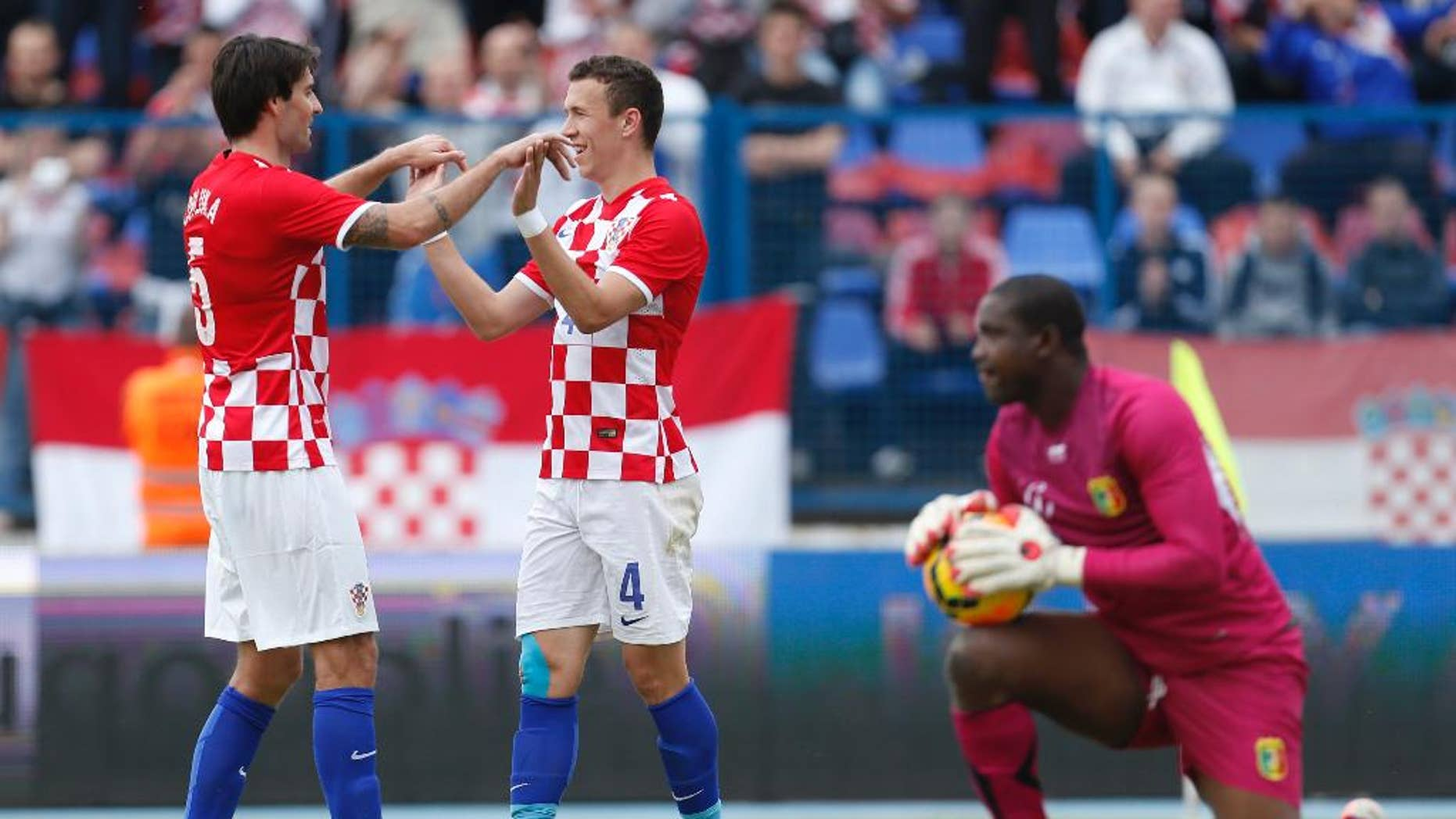 Croatia'sIvan Perisic, center, celebrates his second goal with Vedran Corluka during the internationa friendly soccer match between Croatia and Mali, in Osijek, Croatia, Saturday, May 31, 2014. (AP Photo/Darko Bandic)