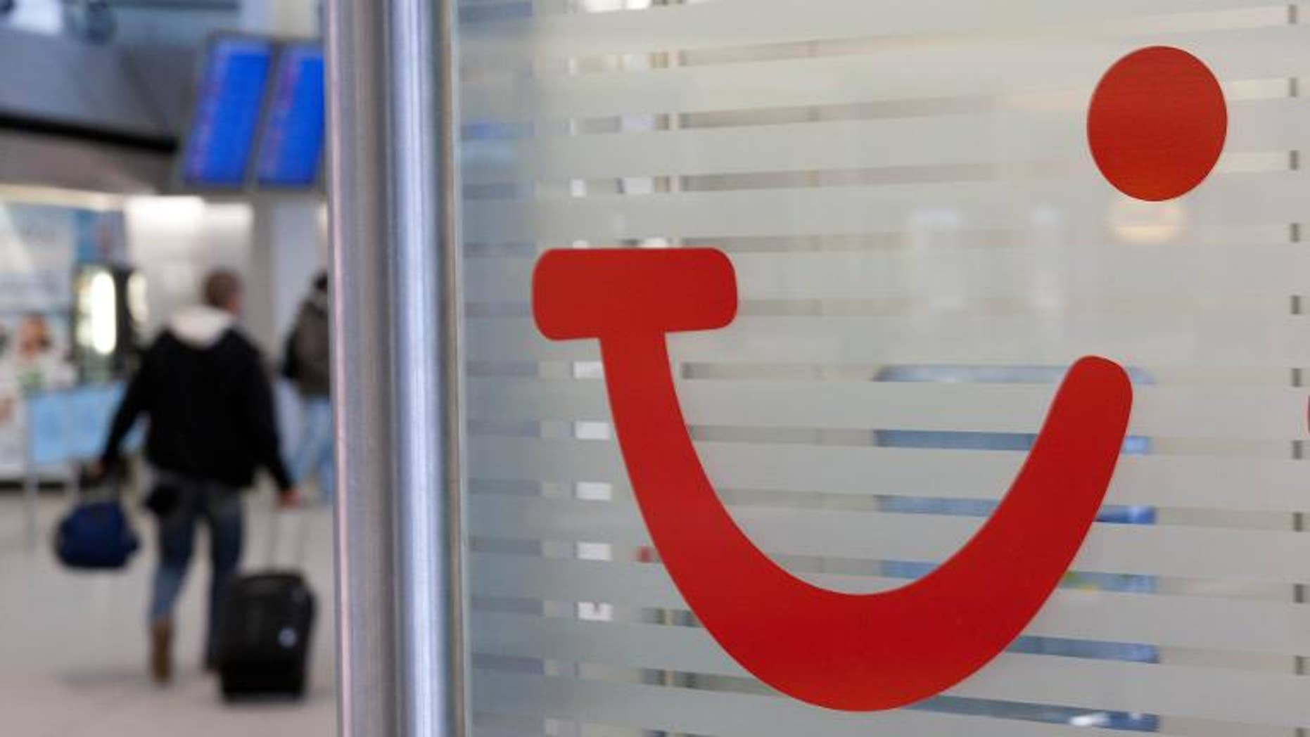 A man walks past the logo of tourism group TUI at Berlin's Tegel Airport on February 4, 2011.