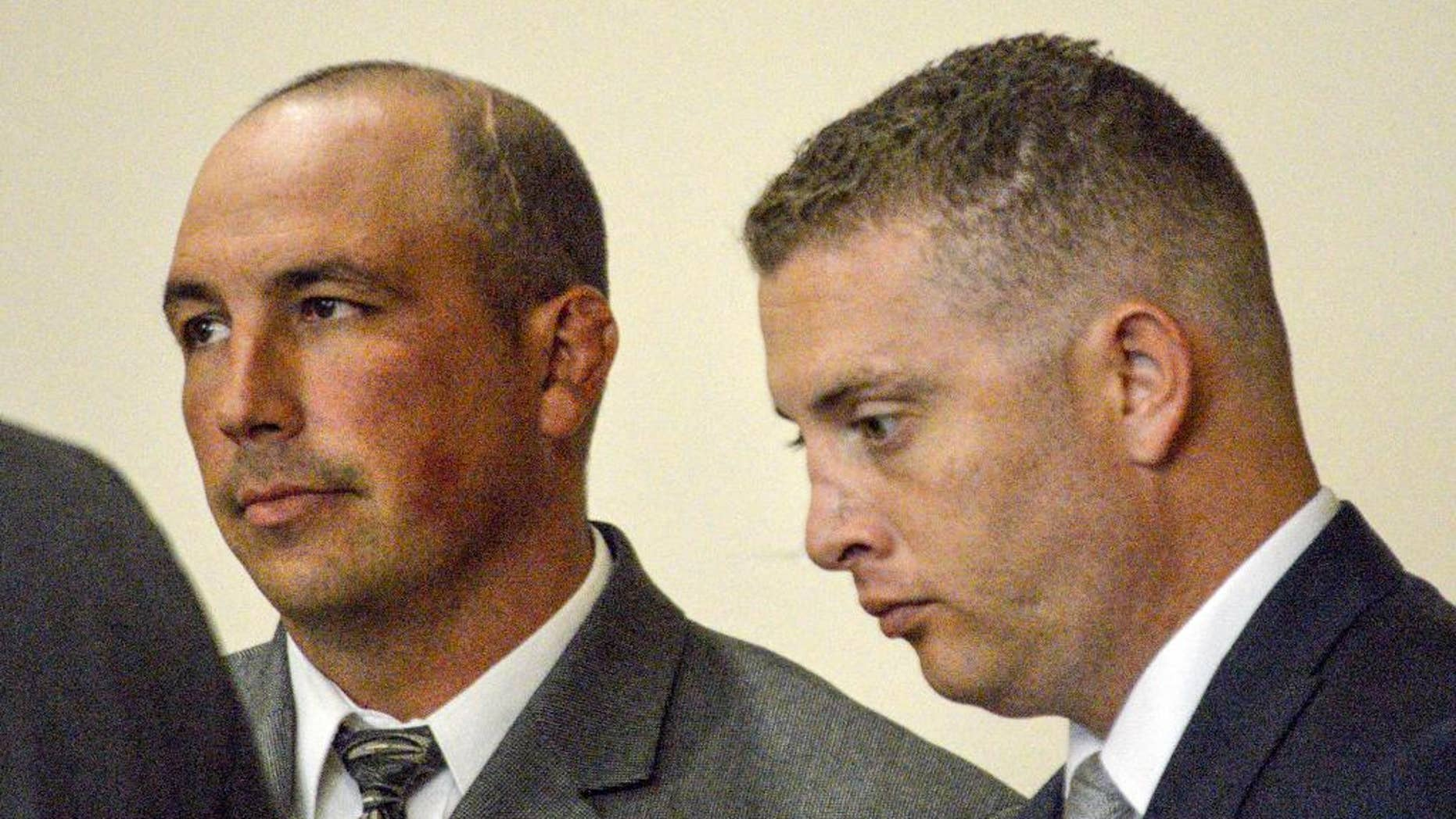 FILE - In this Aug. 18, 2015 file photo, former Albuquerque Police detective Keith Sandy, left, and Officer Dominique Perez speak with attorneys during a preliminary hearing in Albuquerque, N.M., on Tuesday, Aug. 18, 2015. They are expected to be arraigned Friday, Sept. 11, 2015 on second-degree murder charges in the on-duty shooting death of a homeless man who authorities say suffered from mental illness.(AP Photo/Russell Contreras, File)