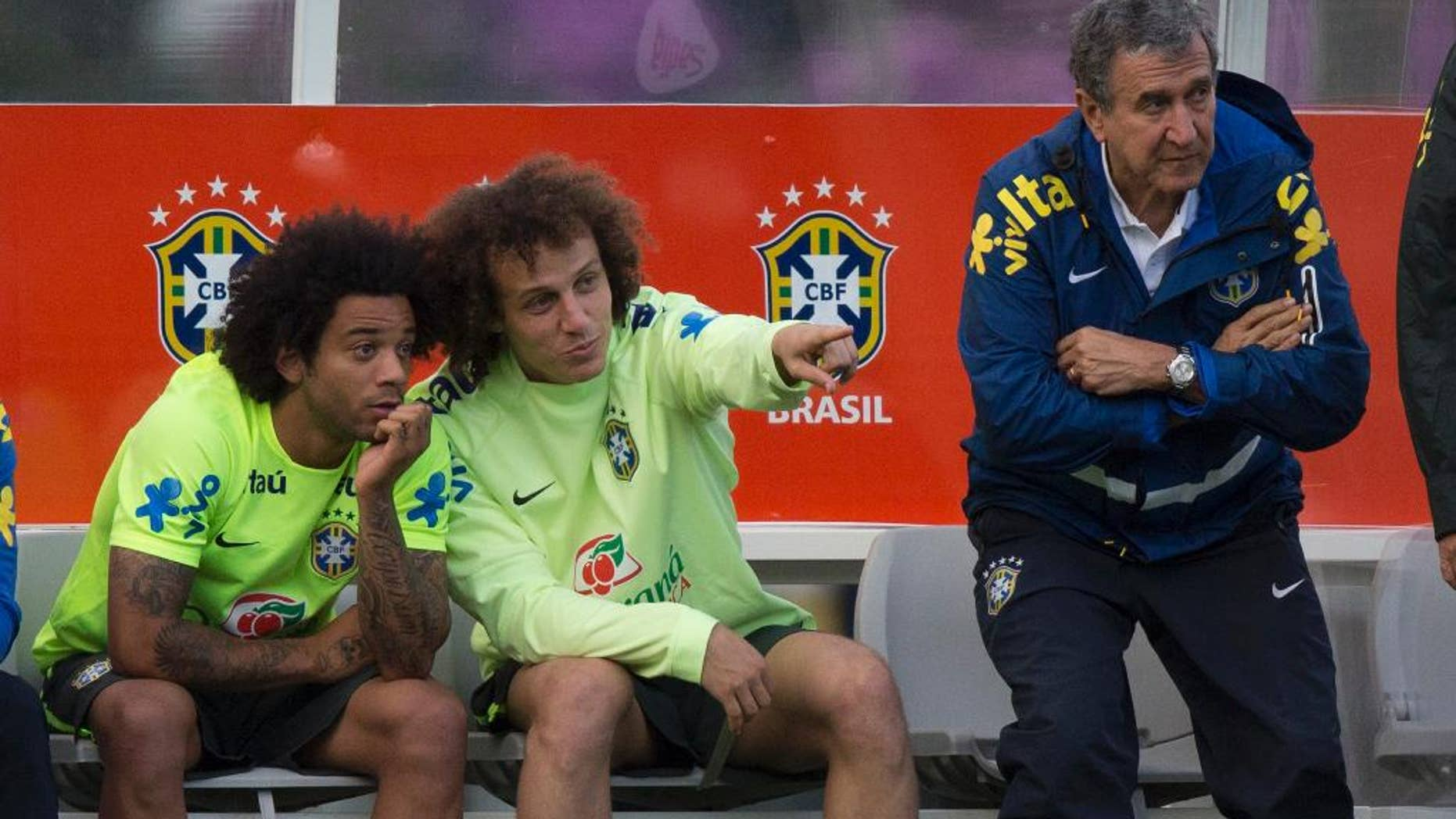 Brazil national soccer team members, David Luiz, center, talks with Marcelo, left, as the Brazil's team coordinator Carlos Alberto Parreira stands next to them, during a practice session at the Granja Comary training center, in Teresopolis, Brazil, Sunday, July 6, 2014. Brazil will face Germany in their World Cup semifinals' match, without superstar soccer player Neymar. (AP Photo/Leo Correa)