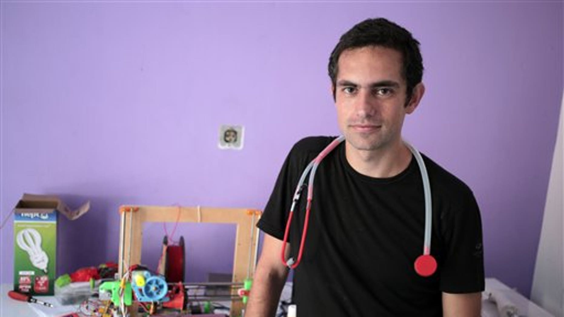In this Monday, Sept. 7, 2015 photo, Dr. Tarek Loubani, a Palestinian-Canadian doctor, poses for a picture with 3D printed stethoscope around his neck, in Gaza City. (AP Photo/ Khalil Hamra)