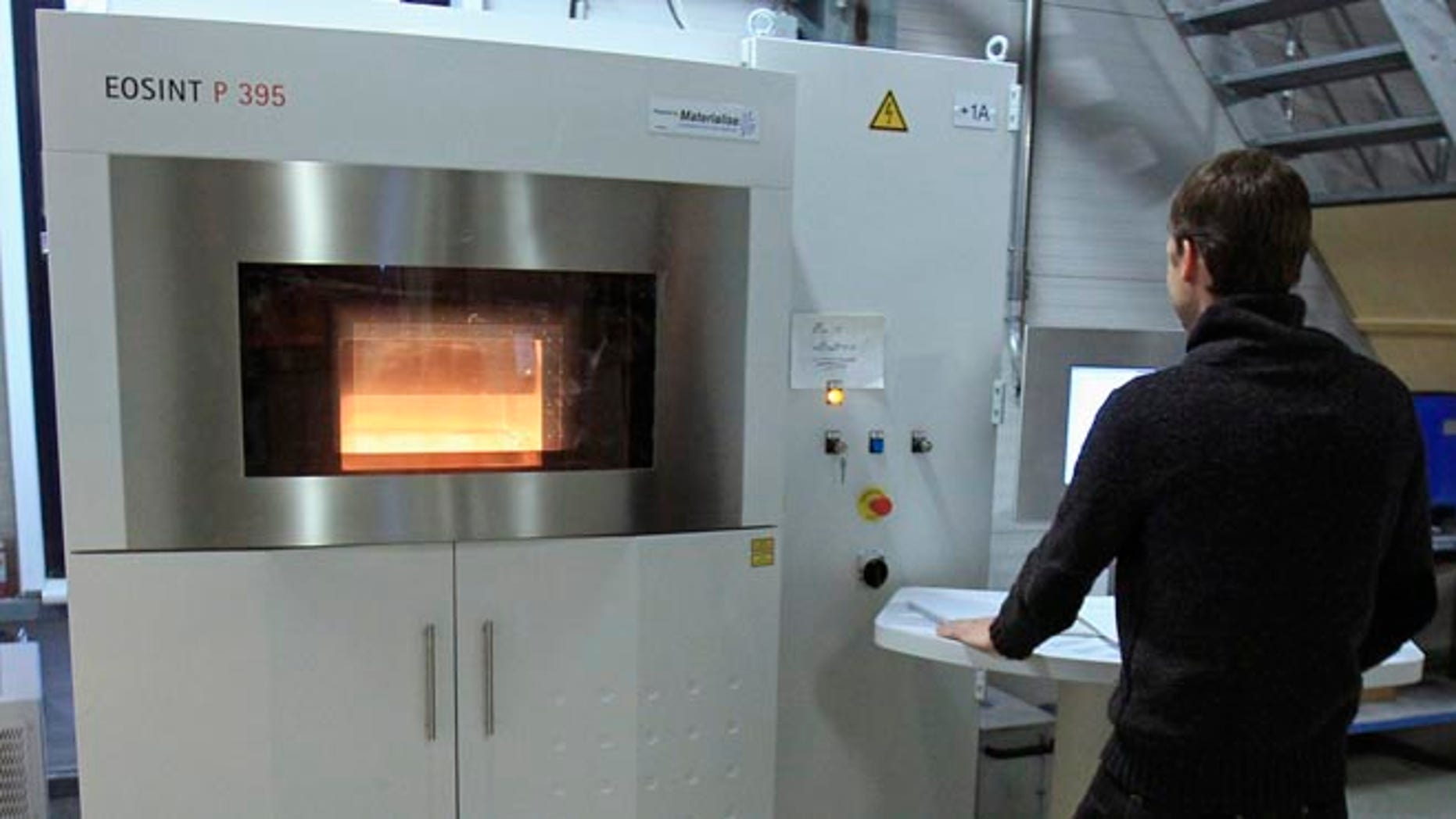 A technician at Belgian company Materialise, the biggest 3D printer in Europe, operates a laser sintering machine that uses high-powered lasers to fuse particles of plastic, layer by layer, to create 3D objects, at the company's headquarters in Leuven.