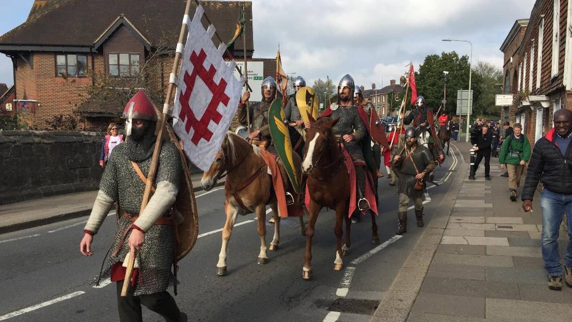 A group of historical re-enactors arrive in Battle, near Hastings, England, Friday Oct. 14, 2016, ending their 300-mile cross-country journey ready to mark the Battle of Hastings which was originaly fought 950-years ago.  The band of re-enactor enthusiasts set out from York, central England, on foot and horseback to simulate the journey by King Harold before the battle in 1066, when Normans under William the Conqueror defeated the English at the Battle of Hastings. (Tom Pugh / PA via AP)
