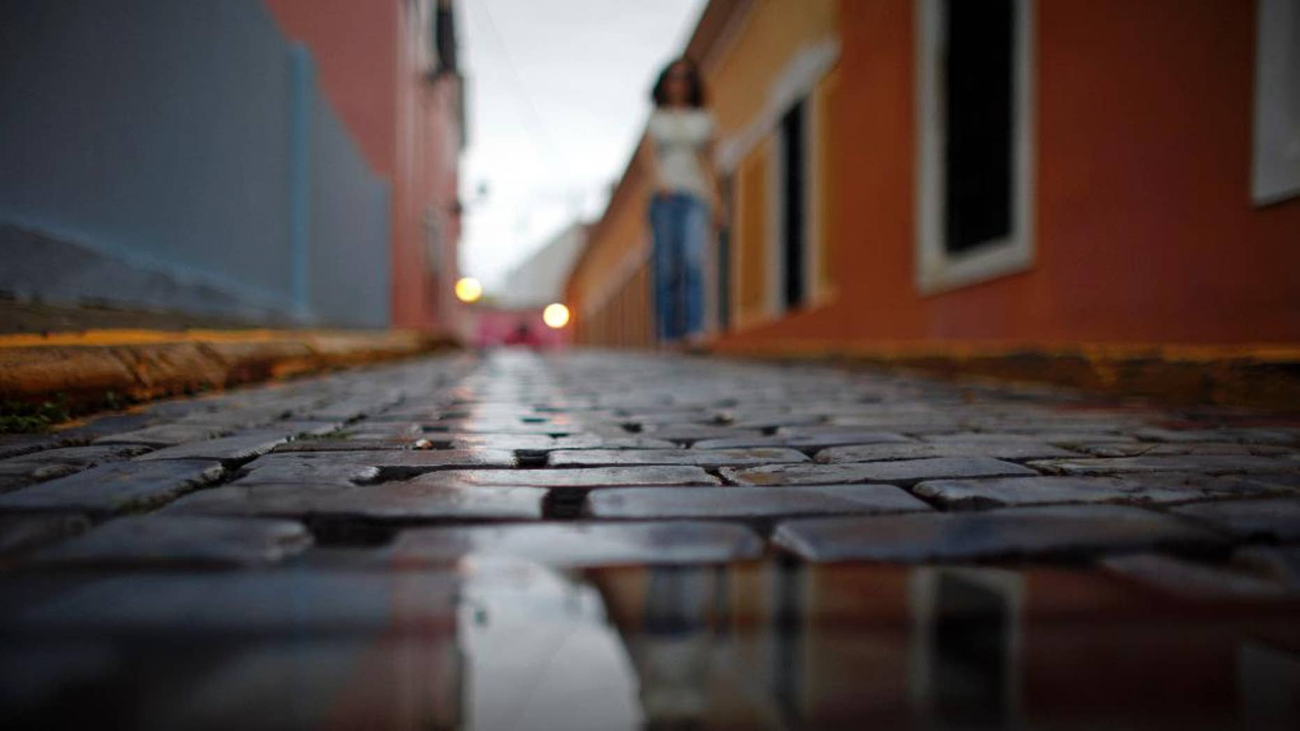 Wet cobblestones are seen on a street during a rainy day in Old San Juan, Puerto Rico, Tuesday, Nov. 4, 2014. Heavy rains caused by a cluster of storms in the northern Caribbean killed at least seven people in Haiti and caused major flooding on Tuesday in the Dominican Republic and Puerto Rico, authorities said. (AP Photo/Ricardo Arduengo)