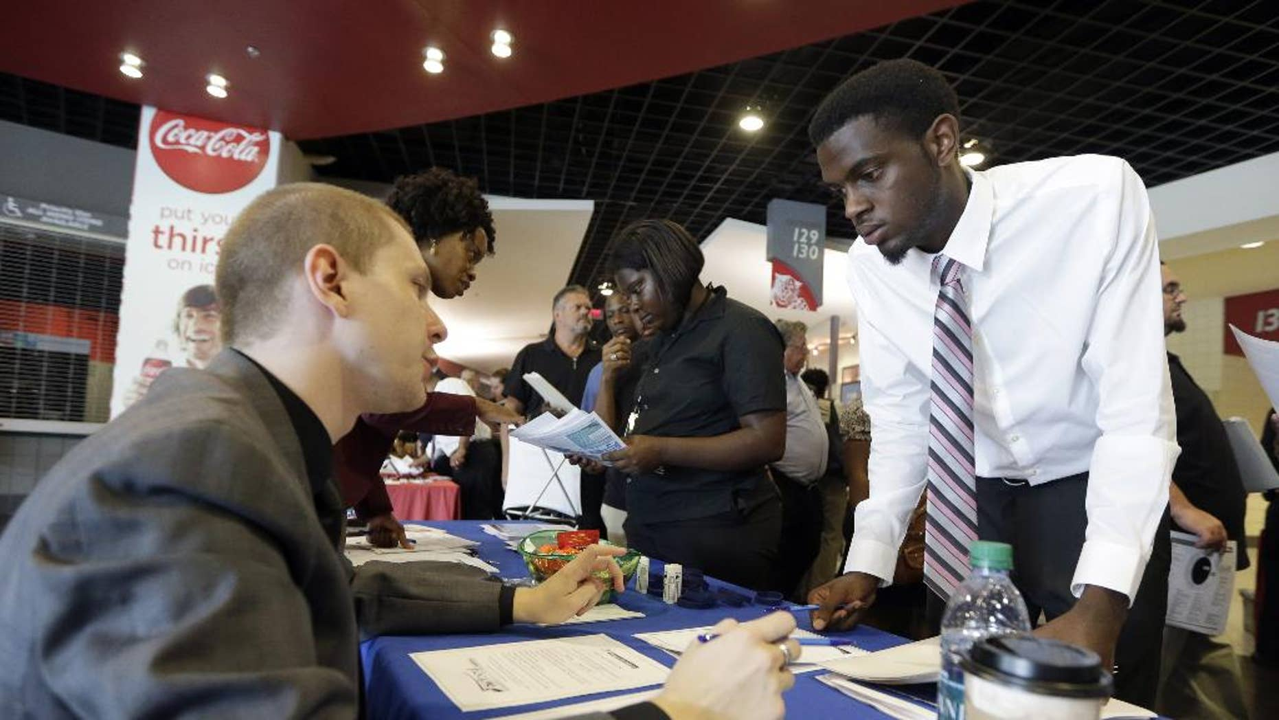 In this photo taken Wednesday, June 10, 2015, job seeker Cory McClain, right, listens to Sam Cucci, of Teleperformance, during a job fair in Sunrise, Fla. The Labor Department reports on the number of people who applied for unemployment benefits for the week ending June 13 on Thursday, June 18, 2015. (AP Photo/Alan Diaz)