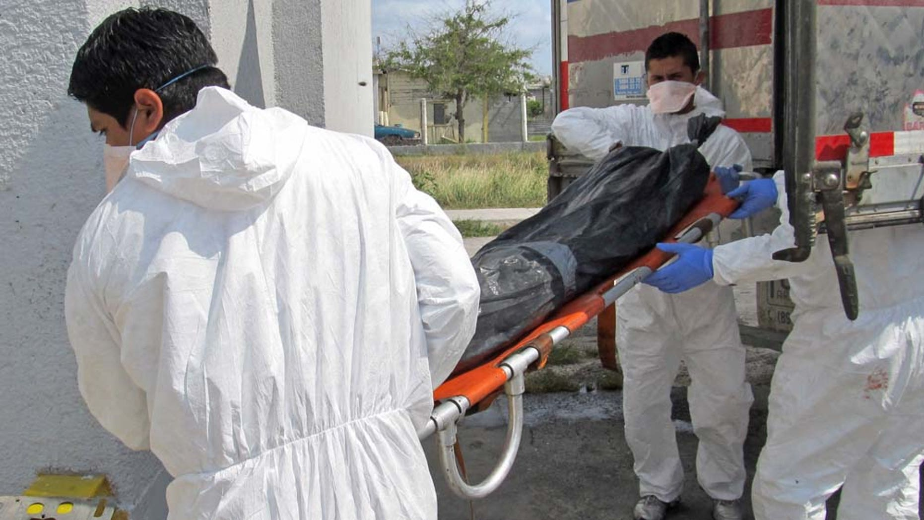 Morgue employees unload a body  from a refrigerated truck into the local morgue in Matamoros, northern Mexico, Wednesday April 13, 2011. Mexican investigators have found a total of 116 bodies in Tamaulipas state in pits near the U.S. border, 28 more than previously reported, Attorney General Marisela Morales said Tuesday. Morales said a total of 17 suspects have been detained in relation to the killings in the northern state of Tamaulipas, some of whom have purportedly confessed to abducting passengers from buses and killing them. (AP Photo/Rubios News)