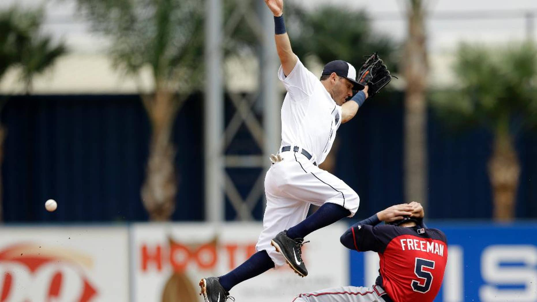 Detroit Tigers second baseman Ian Kinsler loses control of the ball as Atlanta Braves first baseman Freddie Freeman, right, slides under for a steal during the third inning of a spring exhibition baseball game in Lakeland, Fla., Tuesday, March 25, 2014. (AP Photo/Carlos Osorio)