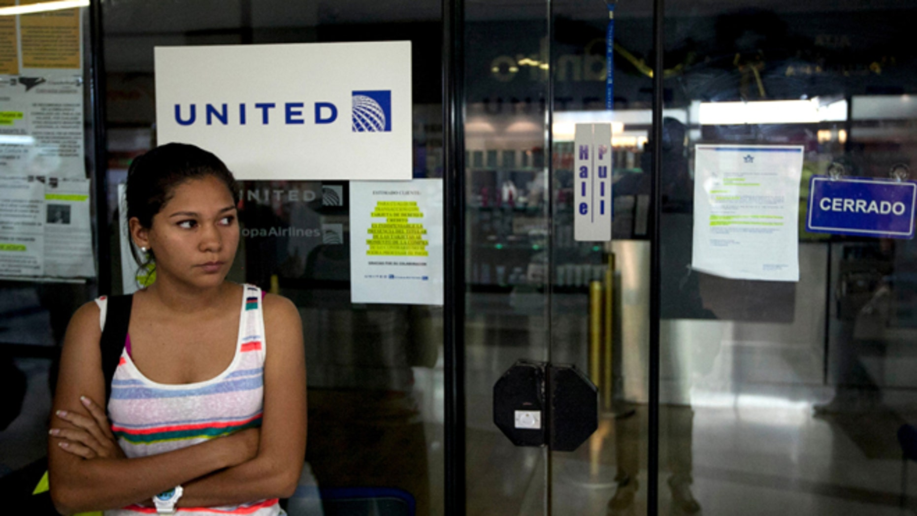 FILE- In this Jan. 24, 2014 file photo, a woman stands outside a closed United Airlines office in Caracas, Venezuela.  Alitalia and Panama's Copa Airlines this May 2014, became the latest carriers to cut flights to Caracas over the socialist government's refusal to allow them to repatriate proceeds from ticket sales inside Venezuela. Foreign airlines say they have the equivalent of $4 billion trapped in the country when sales are converted at the official exchange rate of 6.3 bolivars per U.S. dollar. (AP Photo/Alejandro Cegarra)