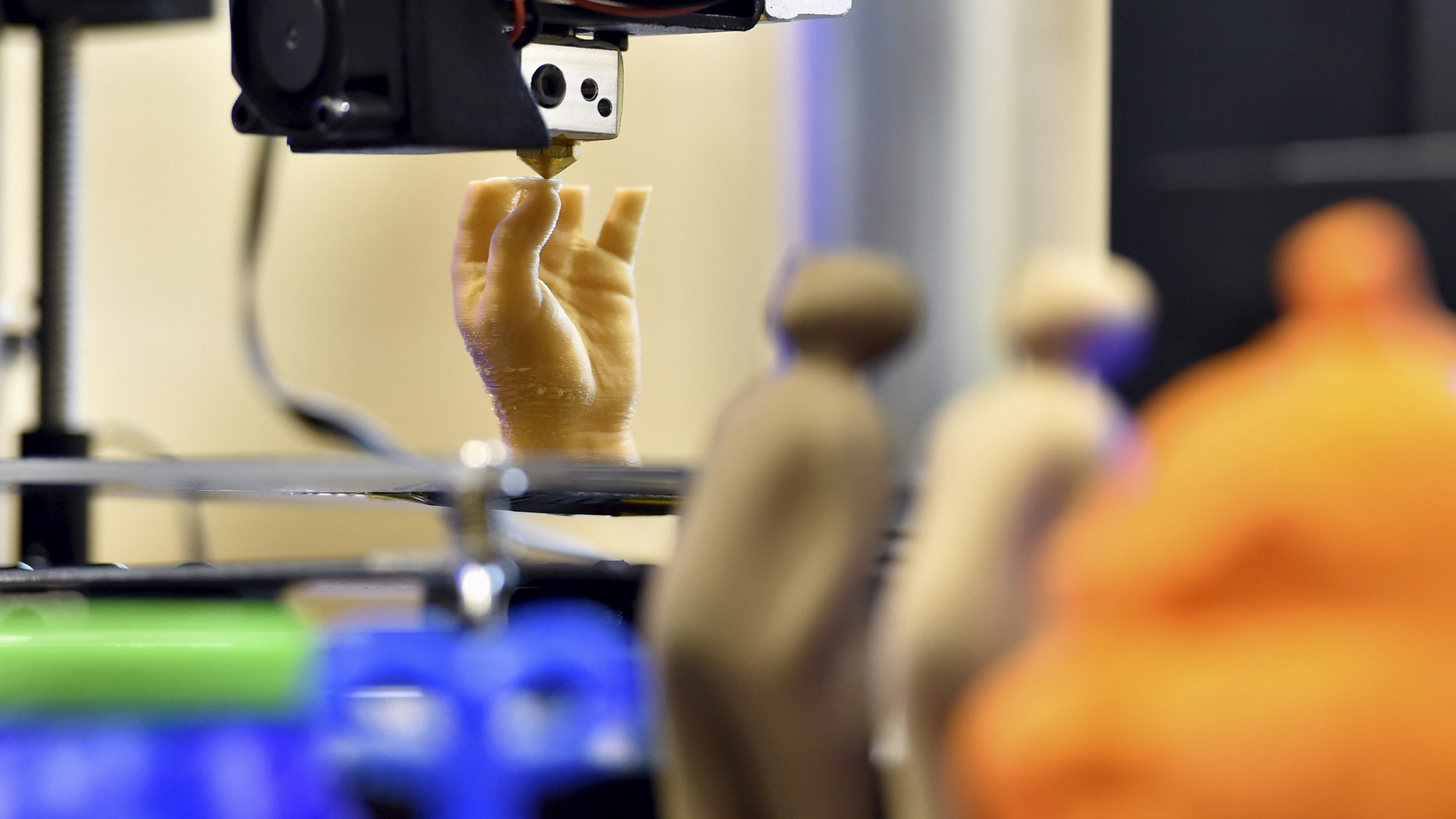 File photo - 3D printed objects are displayed as an artificial hand is being printed during a 3D printing show in Brussels, Belgium, Oct. 18, 2015. (REUTERS/Eric Vidal)