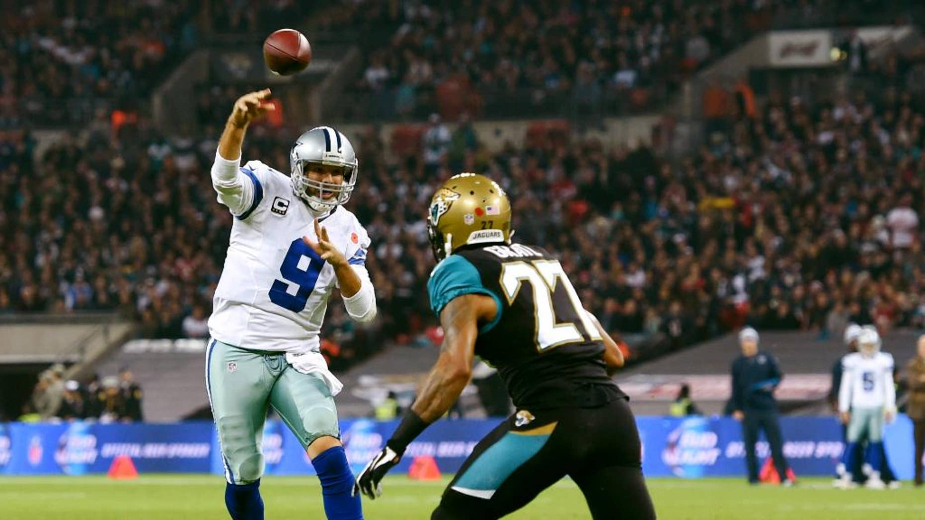 Jacksonville Jaguars wide receiver Cecil Shorts (84) is pursued by Dallas Cowboys defensive back Sterling Moore (26) and free safety J.J. Wilcox (27)  during the first half of an NFL football game at Wembley Stadium, London, Sunday, Nov. 9, 2014. (AP Photo/Tim Ireland)