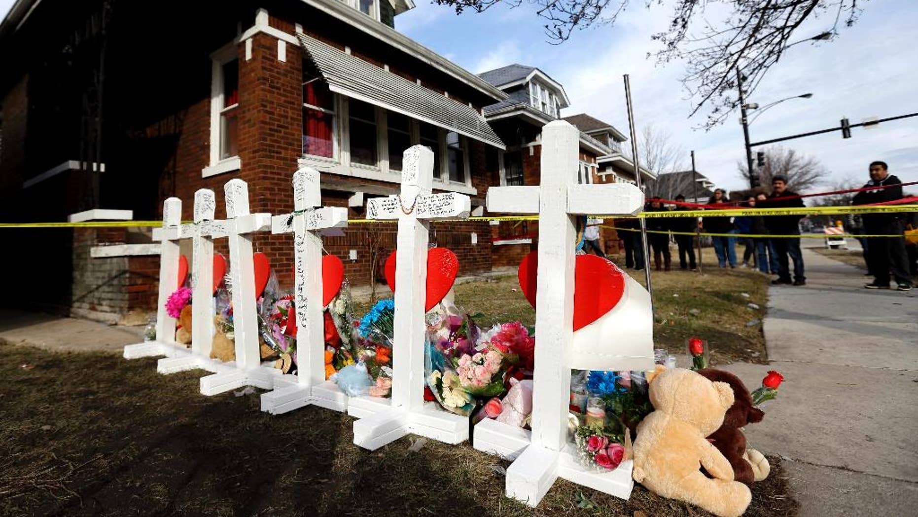 FILE - In this Feb. 7, 2016 file photo, mourners pay their respect outside a home in Chicago where six family members were found dead. On Thursday, May 19, 2016, Chicago police say they have arrested two suspects, a man and woman, in the Feb. 4 slayings. (AP Photo/Nam Y. Huh, File)