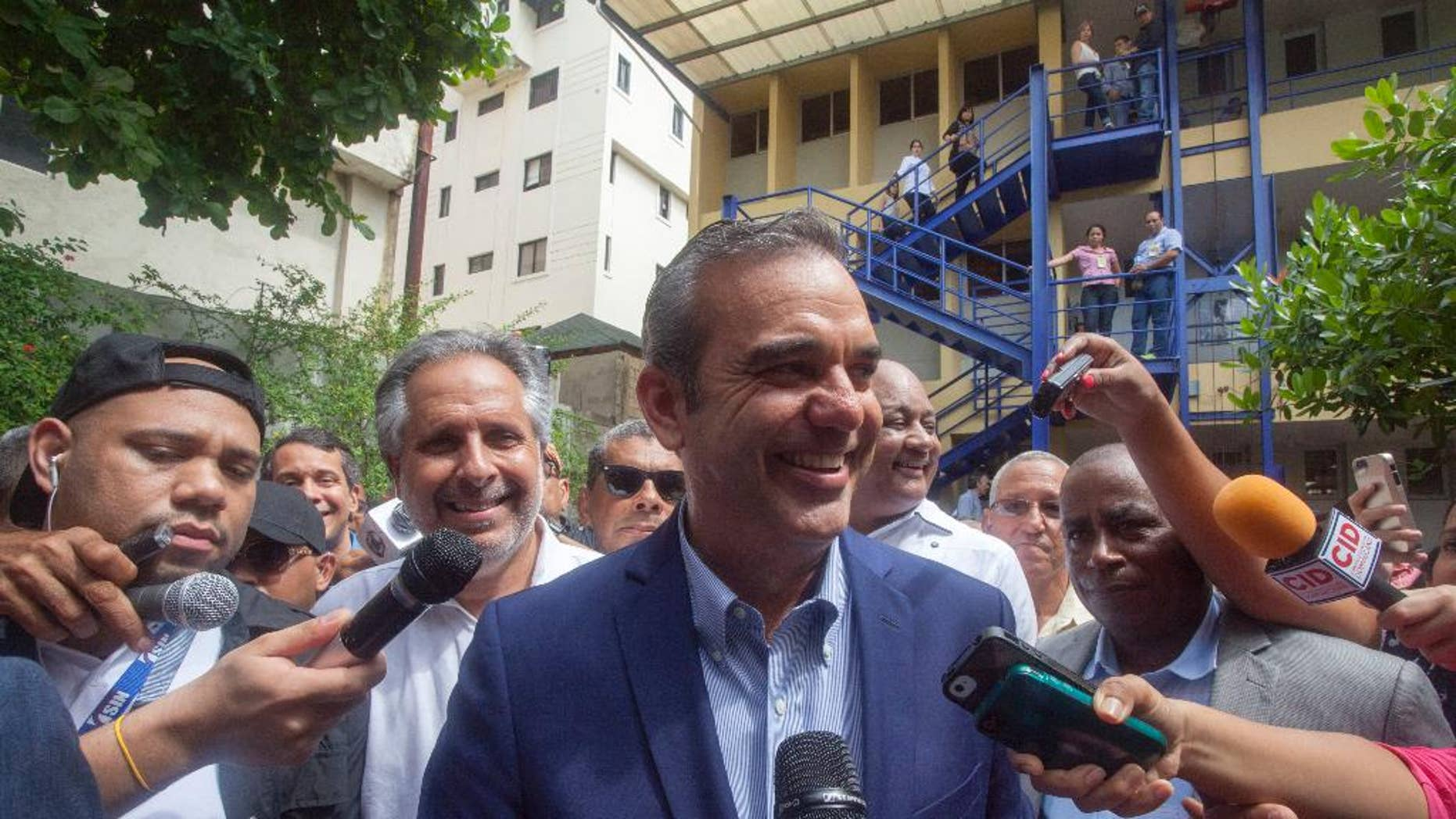 Luis Abinader, center, presidential candidate of the opposition Modern Revolutionary Party, speaks to the press after voting at the presidential, congressional and municipal elections in Santo Domingo, Dominican Republic, Sunday, May 15, 2016. Dominicans faced a dizzying array of choices Sunday in one of the most complex ballots in recent history, with eight candidates for president, all 222 members of Congress up for re-election and thousands of people vying for local offices around the country. Second from left behind Abinader is candidate for Mayor Alberto Atallah.(AP Photo/Tatiana Fernandez)