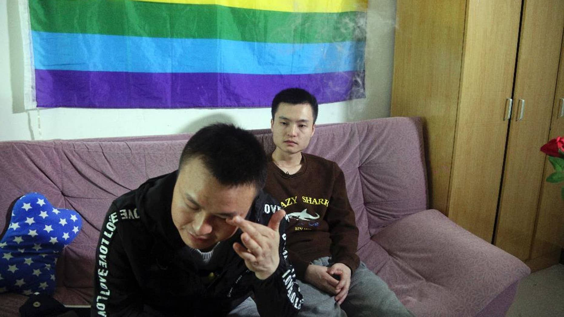 Sun Wenlin, right, sits with his partner Hu Mingliang at home.