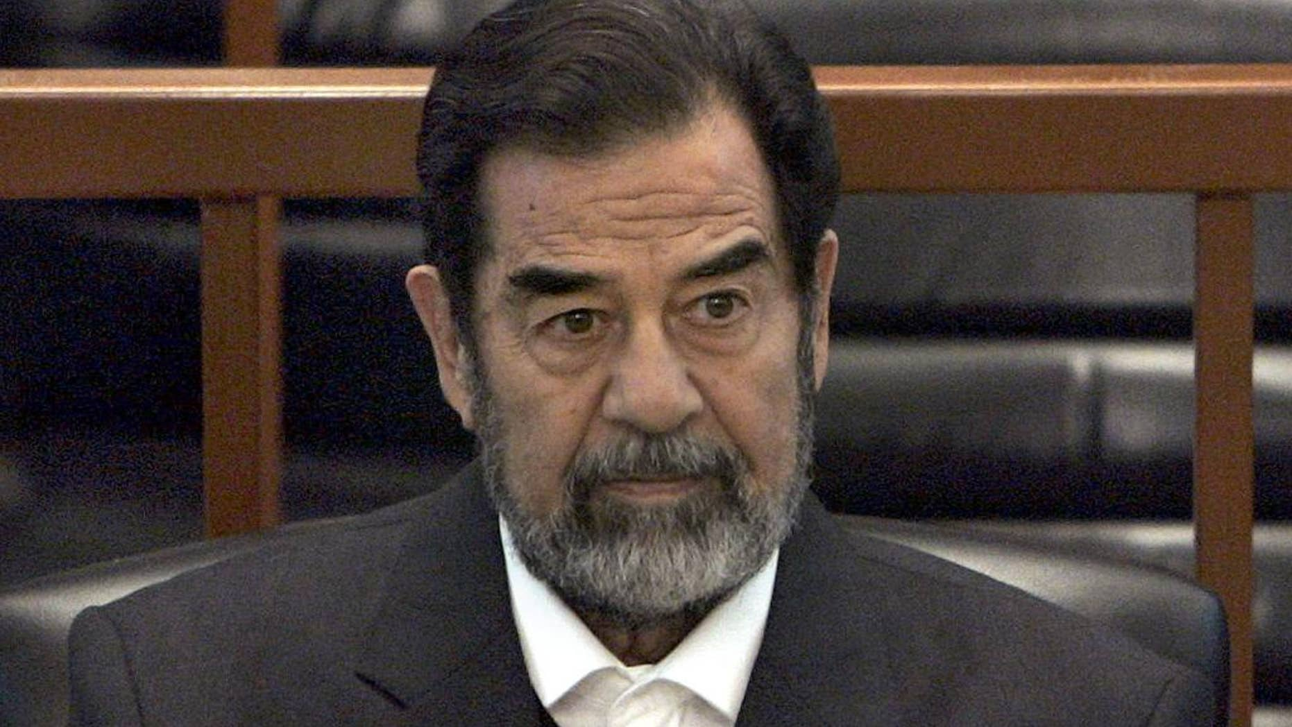 """FILE - In this Dec. 6, 2006 file photo, former Iraq leader Saddam Hussein sits in court in Baghdad, Iraq, during the """"Anfal"""" trial against him. Republican Donald Trump is again praising the former Iraqi President Hussein's ruthlessness, saying he killed terrorists """"so good."""" Trump was speaking at a rally Tuesday, July 5, 2016, in North Carolina when he turned to the former Iraqi leader. (AP Photo/Chris Hondros, Pool, File)"""