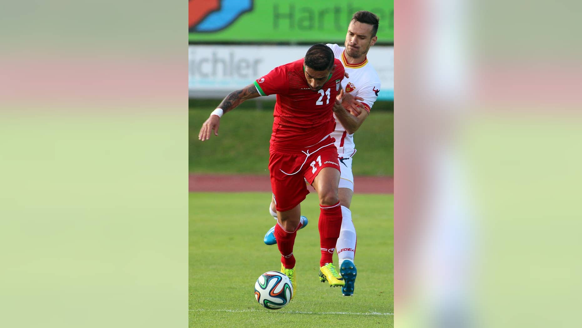 Iran's Ashkan Dejagah, left, challenges for a ball with Marko Vesovic, right, of Montenegro during a friendly soccer match between Iran and Montenegro, in Hartberg, Austria, Monday, May 26, 2014. (AP Photo/Ronald Zak)