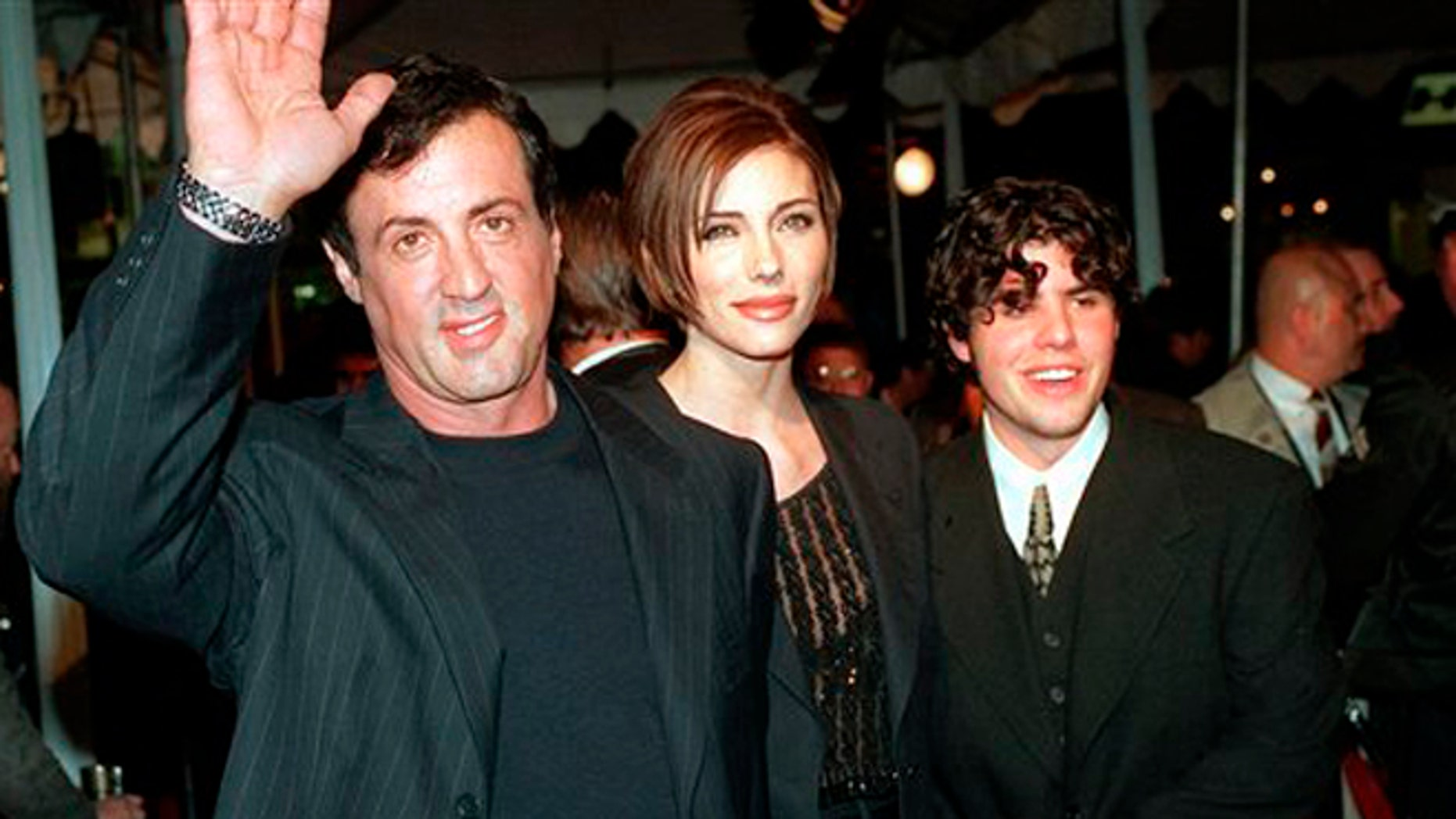 "Dec. 5, 1996: In this file photo, Sylvester Stallone, left, star of the film ""Daylight,"" arrives at the film's world premiere with his girlfriend Jennifer Flavin, center, and his son Sage Stallone, who co-stars in the film, in Hollywood district of Los Angeles."